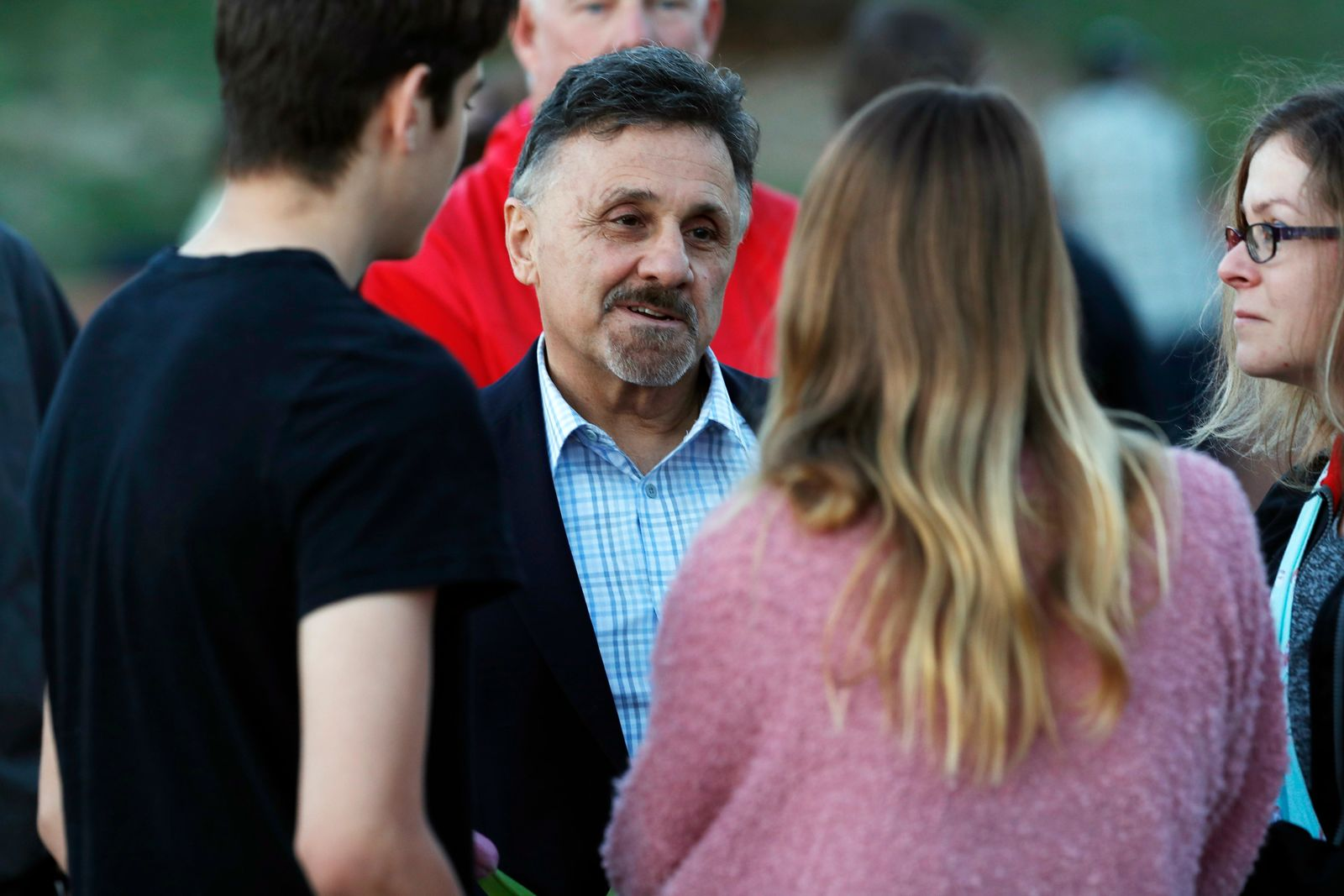 FILE - In this Friday, April 19, 2019, file photograph, Frank DeAngelis, center, greets well-wishers during a vigil at the memorial for victims of the massacre at Columbine High School more than 20 years earlier in Littleton, Colo. DeAngelis was principal of the school at the time of the attack. The school district is considering razing the current building and putting up a new structure. (AP Photo/David Zalubowski, File)