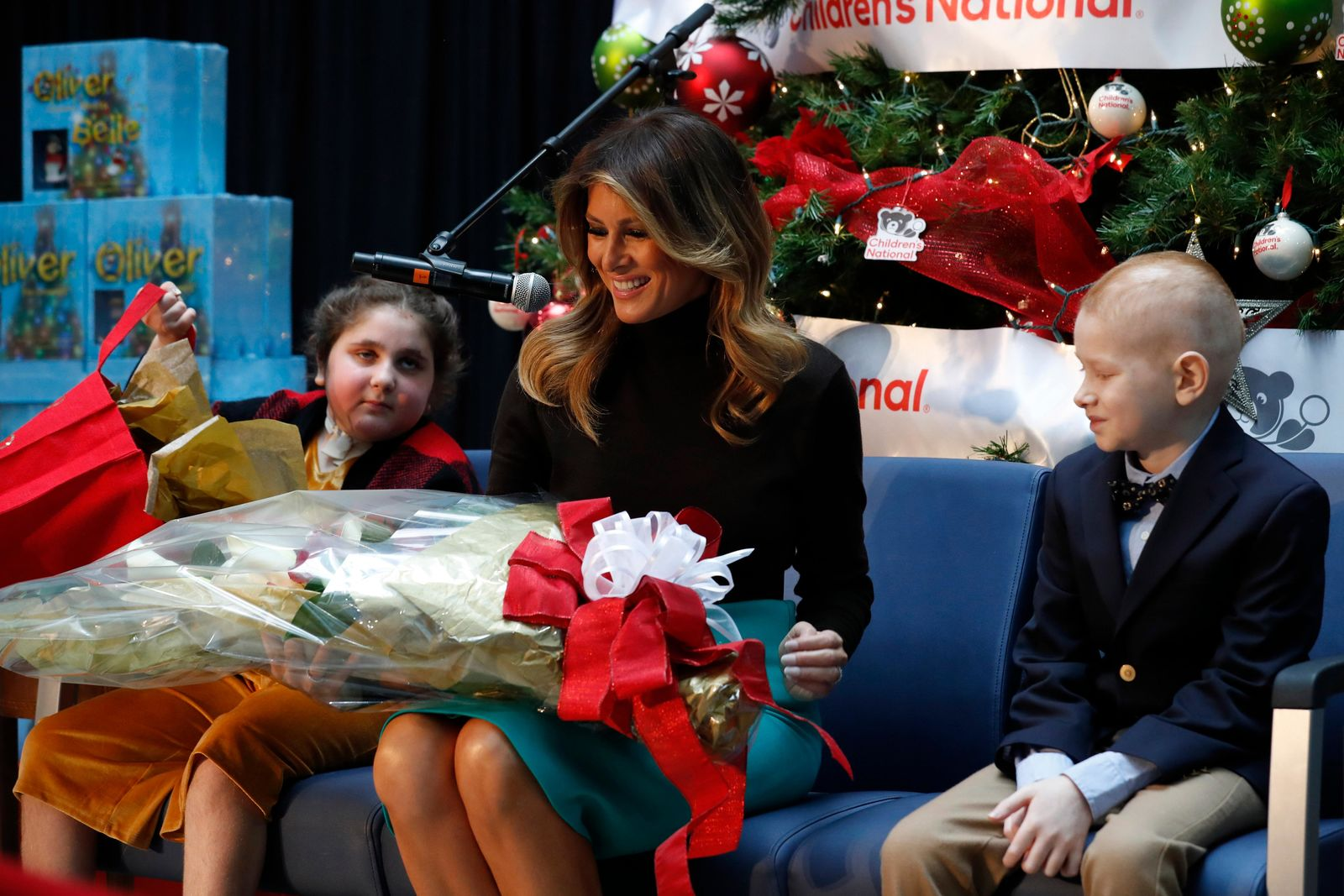 First lady Melania Trump reacts as she receives gifts from patients at Children's National Hospital, Sammie Burley, left, and Declan McCahan, right, Friday, Dec. 6, 2019, after reading a Christmas book to children at the hospital in Washington. (AP Photo/Jacquelyn Martin)