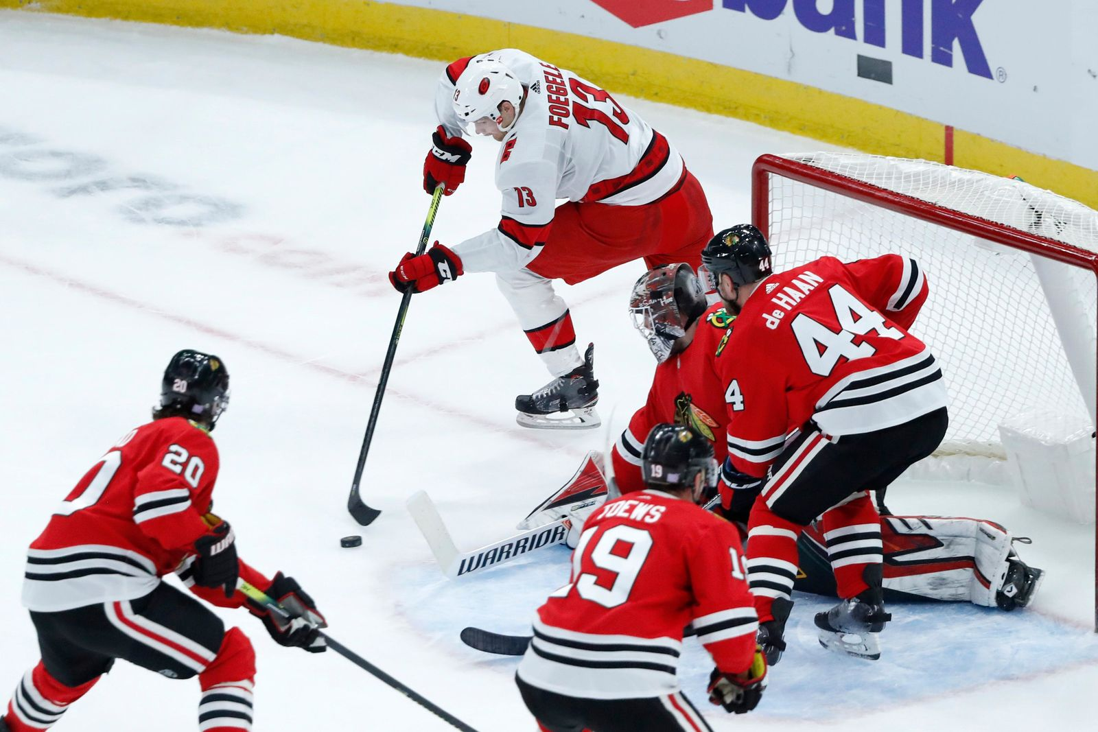 Carolina Hurricanes left wing Warren Foegele (13) takes a backhand shot on goal as Chicago Blackhawks defend during the first period of an NHL hockey game Tuesday, Nov. 19, 2019, in Chicago. (AP Photo/Charles Rex Arbogast)