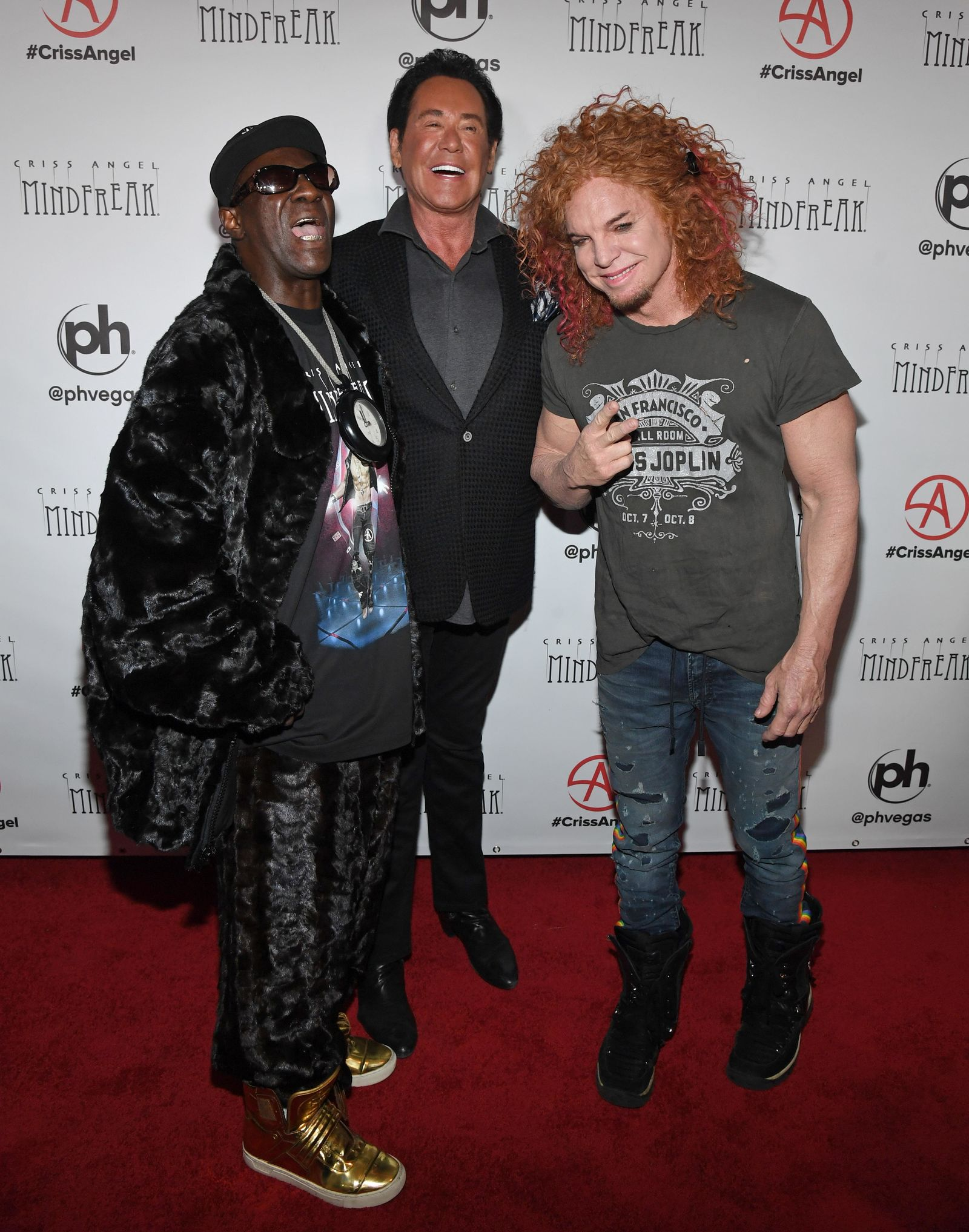 "LAS VEGAS, NEVADA - JANUARY 19:  (L-R) Rapper Flavor Flav, entertainer Wayne Newton and comedian Carrot Top attend the grand opening of ""Criss Angel MINDFREAK"" at Planet Hollywood Resort & Casino on January 19, 2019 in Las Vegas, Nevada.  (Photo by Ethan Miller/Getty Images for Planet Hollywood Resort & Casino)"