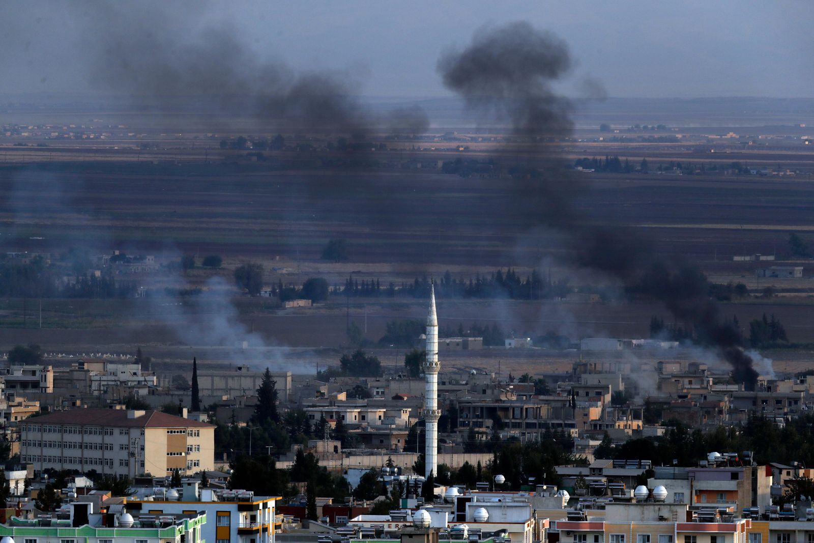In this photo taken from the Turkish side of the border between Turkey and Syria, in Ceylanpinar, Sanliurfa province, southeastern Turkey, smoke billows from targets in Ras al-Ayn, Syria, caused by bombardment by Turkish forces, Tuesday, Oct. 15, 2019. (AP Photo/Lefteris Pitarakis)