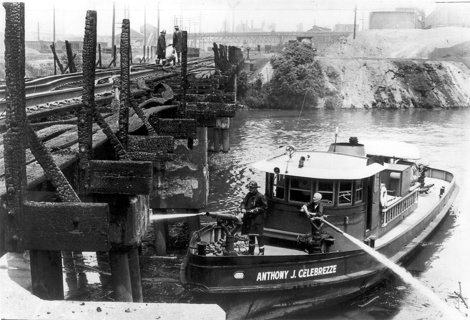 "Cleveland firefighters aboard the Anthony J. Celebrezze fire boat extinguish hot spots on a railroad bridge torched by burning fluids and debris on the Cuyahoga River in 1969, in Cleveland. Fifty years after the Cuyahoga River's famous fire, a plucky new generation of Cleveland artists and entrepreneurs has turned the old jokes about the ""mistake on the lake"" into inspiration and forged the decades of embarrassment into a fiery brand of local pride. (Mitchell Zaremba/The Plain Dealer via AP)"