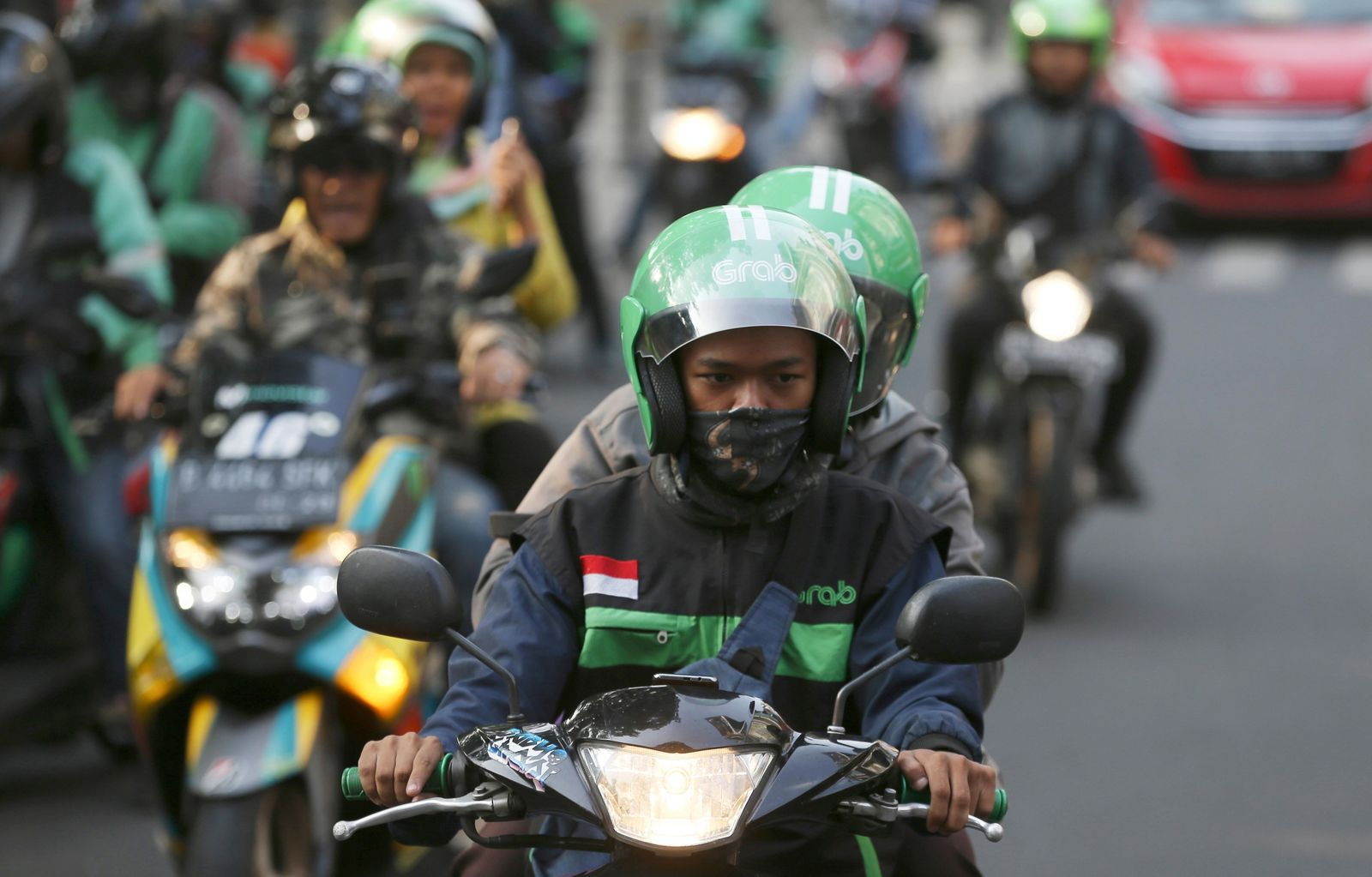 A Grab driver rides on his motorcycle in Jakarta, Indonesia, Monday, July 29, 2019. Japanese technology company Softbank and Southeast Asian ride hailing app Grab said Monday, July 29, 2019, they're investing $2 billion in Indonesia over the next five years. (AP Photo/Achmad Ibrahim)