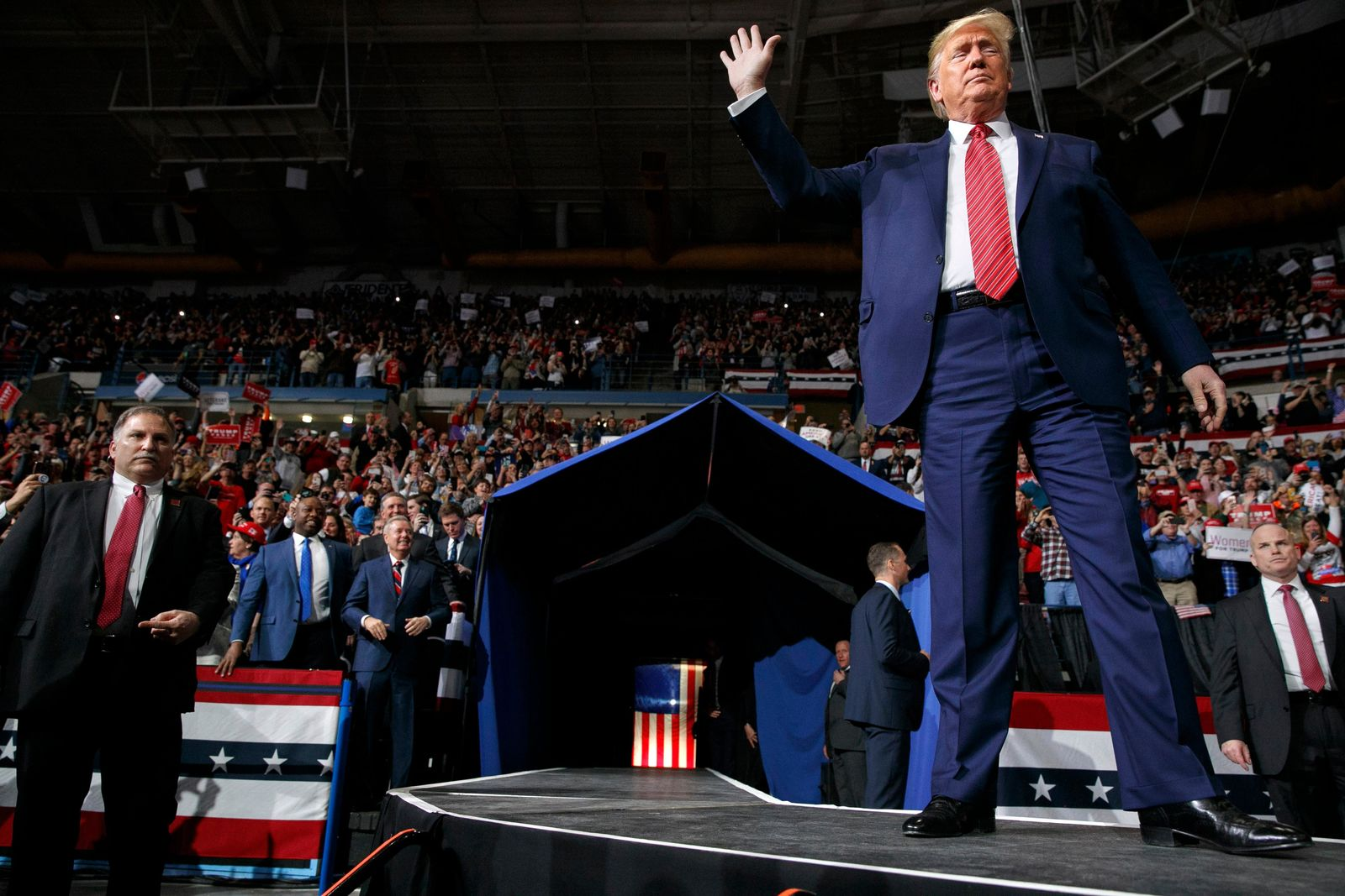 President Donald Trump waves as he arrives in North Charleston, S.C., for a campaign rally, Friday Feb. 28, 2020. Attending the rally are Sen. Lindsey Graham, R-S.C., center, and Sen. Tim Scott, R-S.C., left. (AP Photo/Jacquelyn Martin)