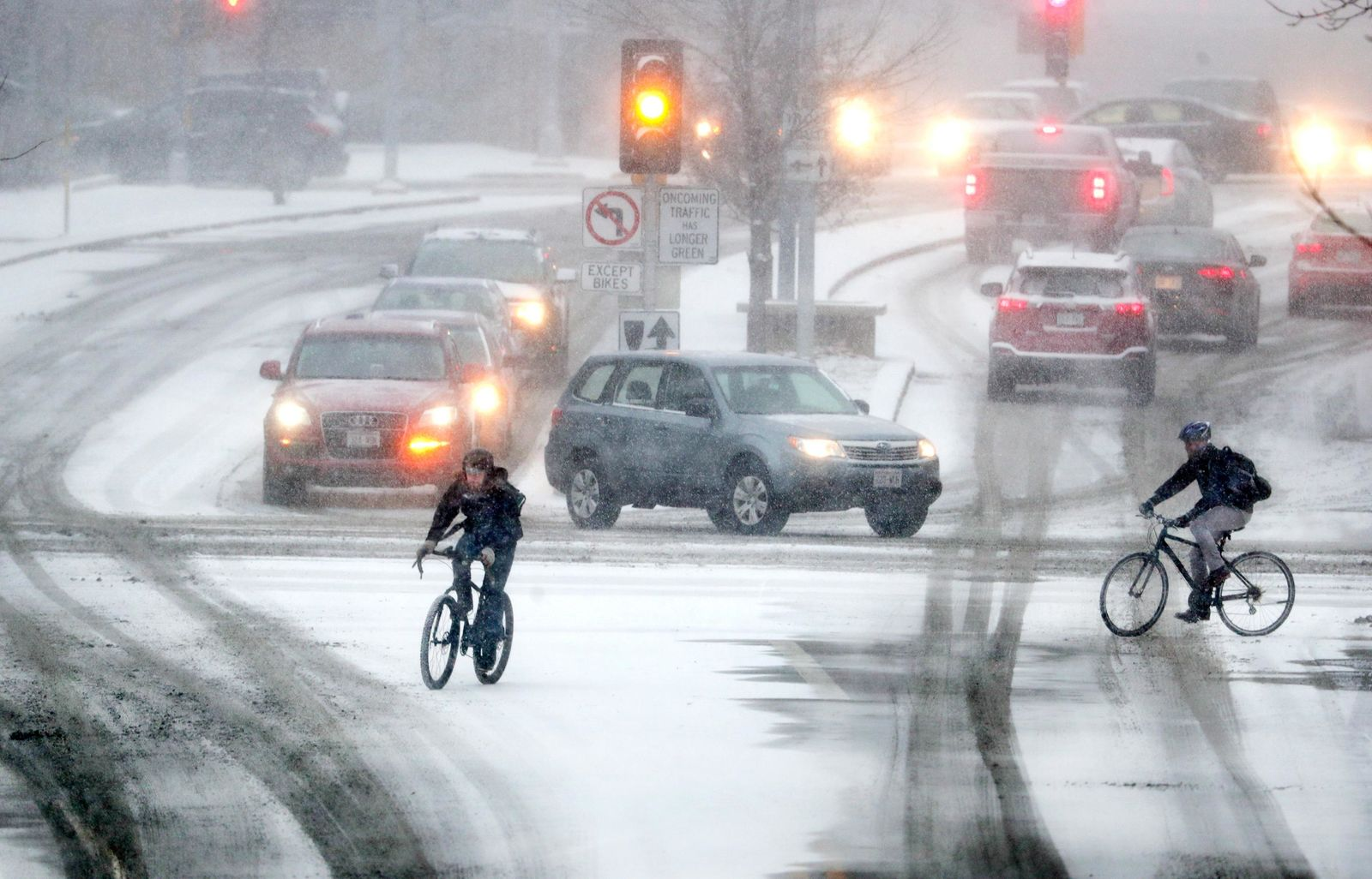 Bikers crossing Park Street at the intersection of University Ave during a late afternoon snow storm Friday, Jan. 18, 2019 in Madison, Wis. (Steve Apps/Wisconsin State Journal via AP)