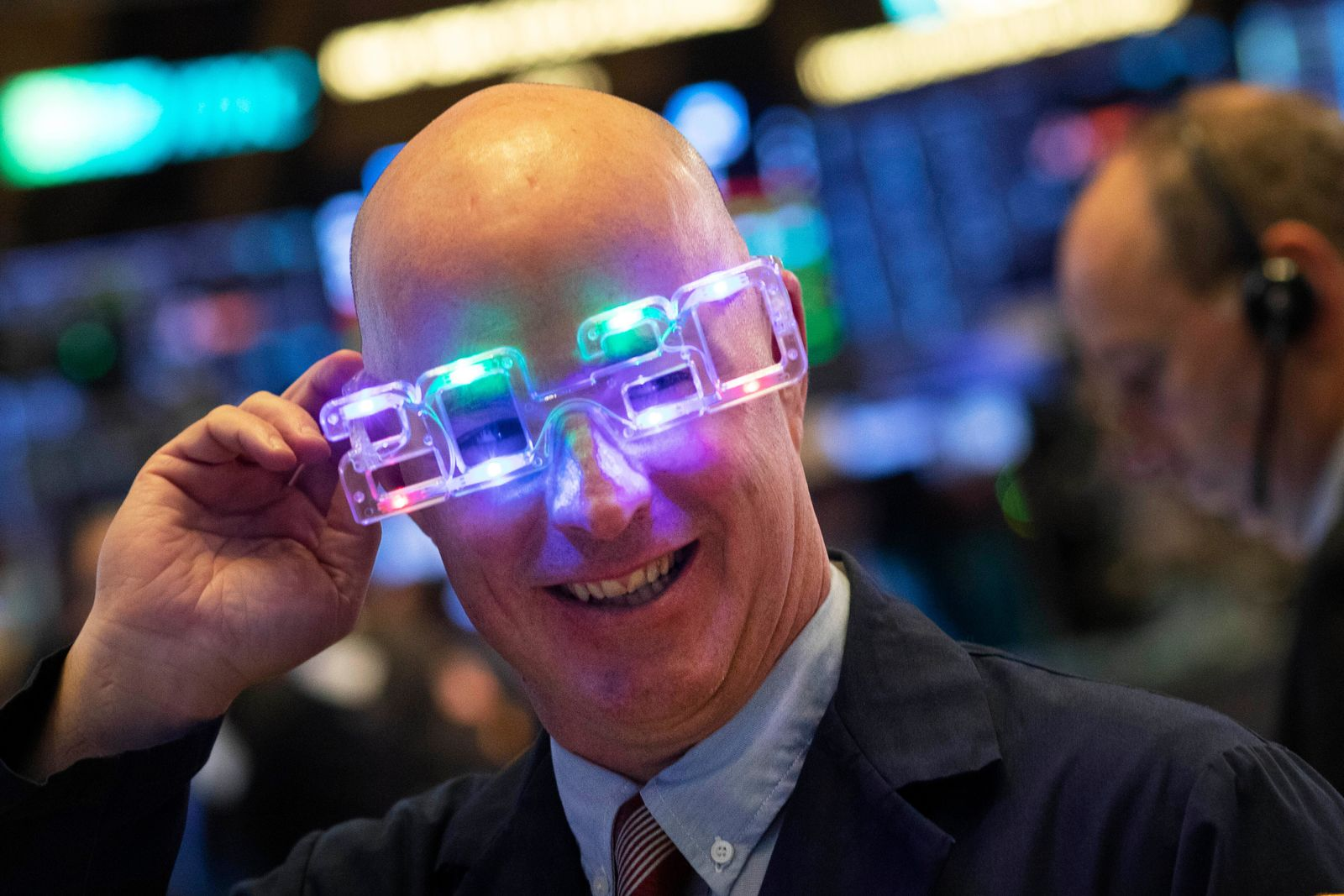 Stock trader John O'Hara tries on his New Year's 2020 party glasses at New York Stock Exchange, Tuesday, Dec. 31, 2019. Stocks slipped globally in quiet New Year's Eve trading Tuesday with many markets closed. Wall Street could close 2019 with back-to-back daily losses in a year that the U.S. posted the largest market gains since 2013. (AP Photo/Mark Lennihan)