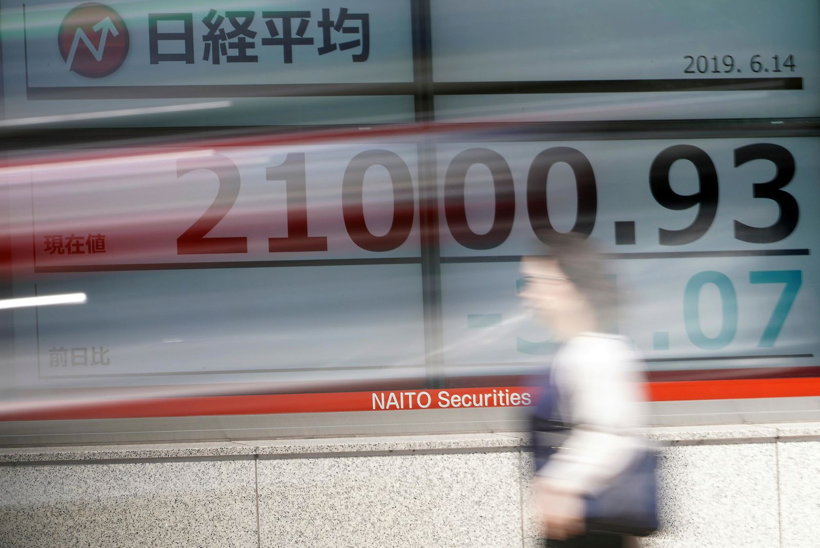 A woman walks past an electronic stock board showing Japan's Nikkei 225 index at a securities firm in Tokyo Friday, June 14, 2019.{ } (AP Photo/Eugene Hoshiko)