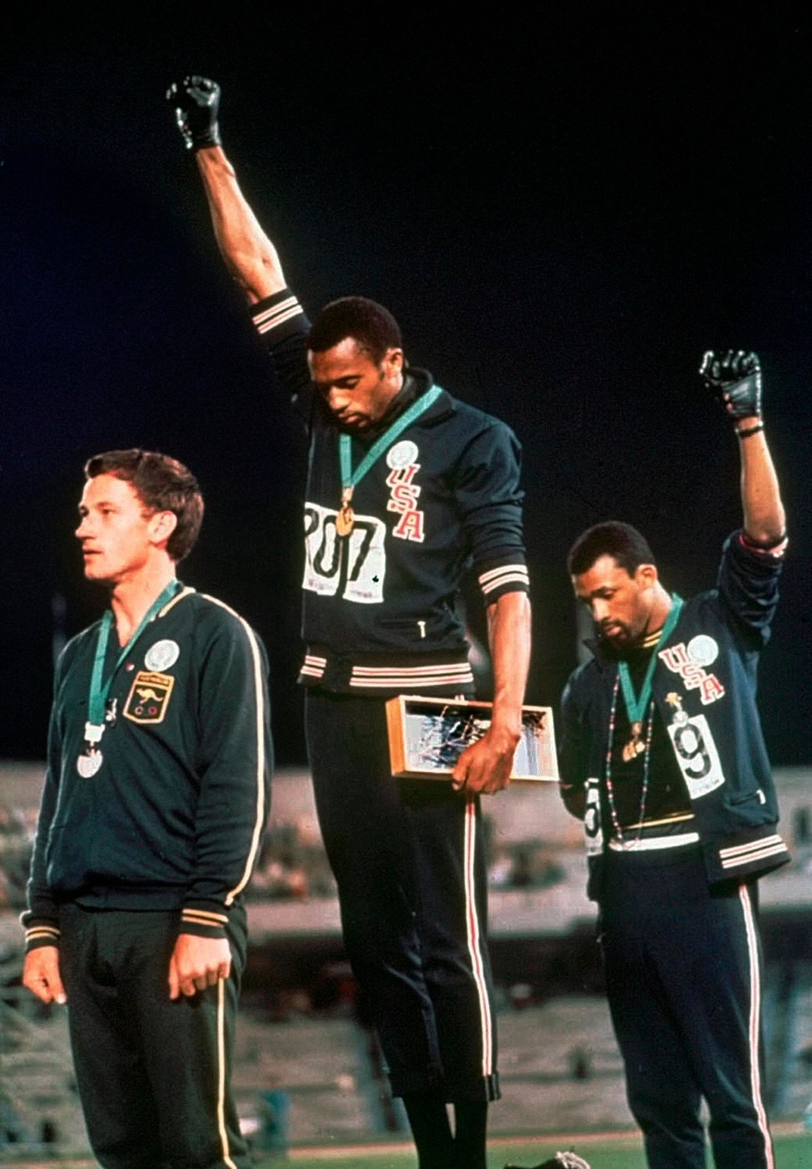 FILE - In this Oct. 16, 1968, file photo, U.S. athletes Tommie Smith, center, and John Carlos stare downward and extend gloved hands skyward in a Black power salute after Smith received the gold and Carlos the bronze for the 200 meter run at the Summer Olympic Games in Mexico City. (AP Photo, File)