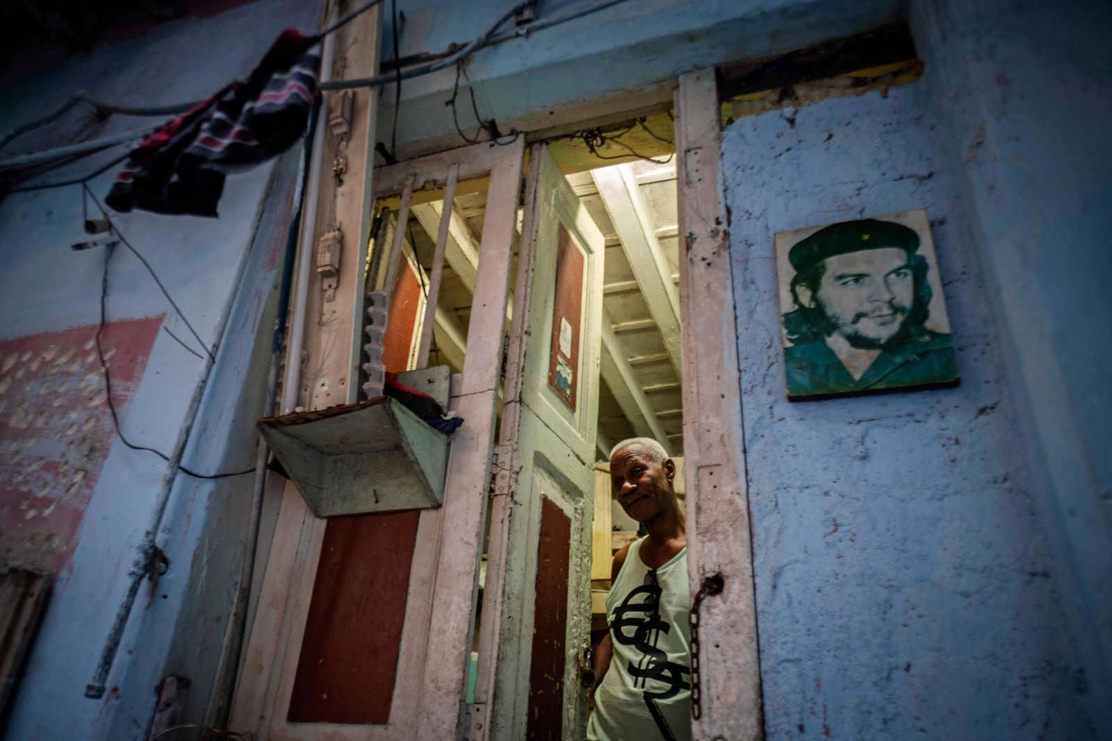 "In this Nov. 10, 2019 photo, Lorenzo Ballester poses at the door of his house, decorated with a photo of revolutionary hero Ernesto ""Che"" Guevara, in Havana, Cuba. The city of Havana will celebrate its 500th anniversary on Nov. 16. (AP Photo/Ramon Espinosa)"