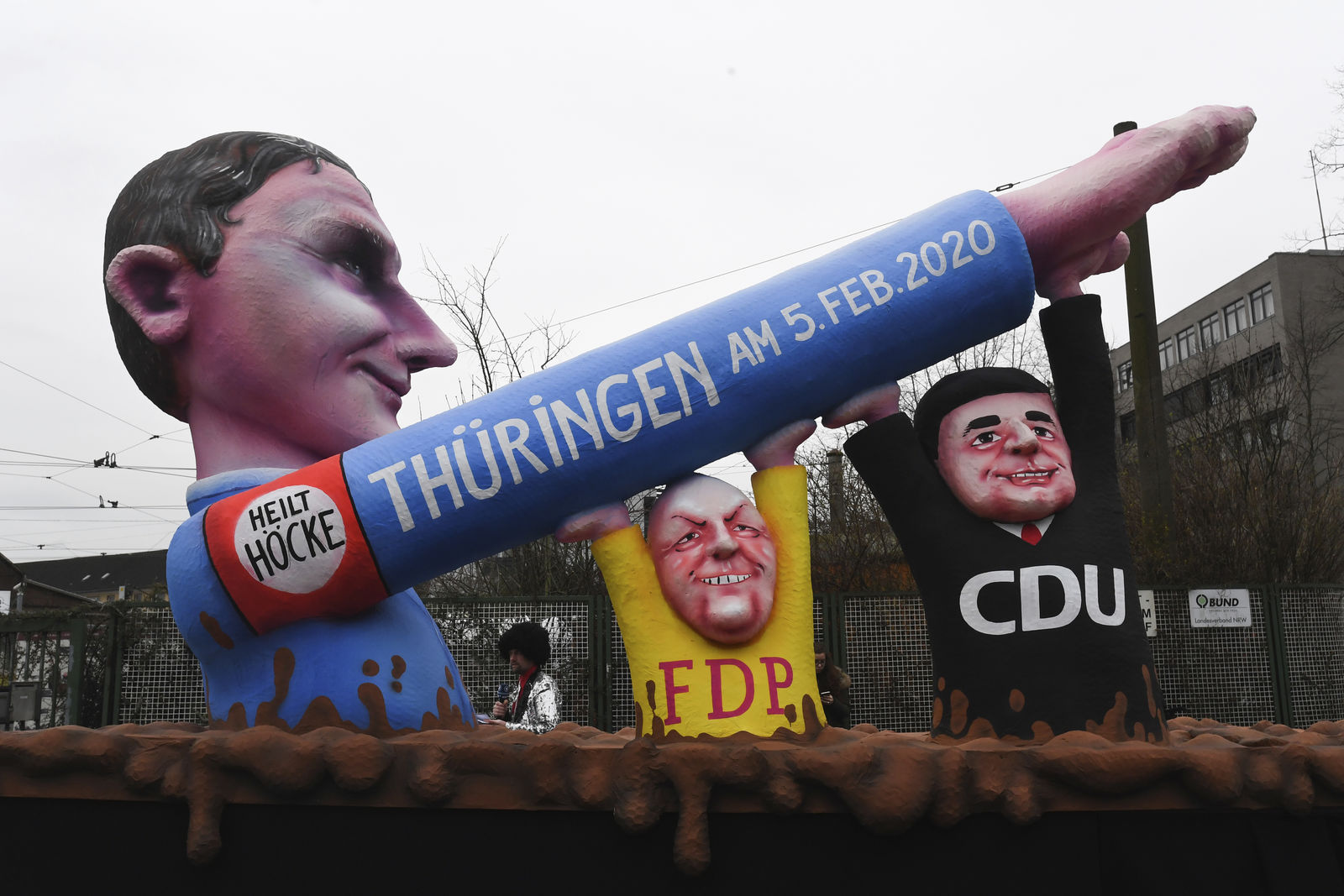"A carnival float featured Alternative for Germany regional leader Bjoern Hoecke,  who called Berlin's memorial to the victims of the Nazi Holocaust a ""monument of shame,"" giving a Nazi salute, with his outstretched stiff arm being held up by figures from Merkel's CDU party and the pro-business FDP at the traditional carnival parade in Duesseldorf, Germany, Monday, Feb 24, 2020. The foolish street spectacles in the carnival centers of Duesseldorf, Mainz and Cologne, watched by hundreds of thousands of people, are the highlights in Germany's carnival season on Rosemonday. (Federico Gambarini/dpa via AP)"