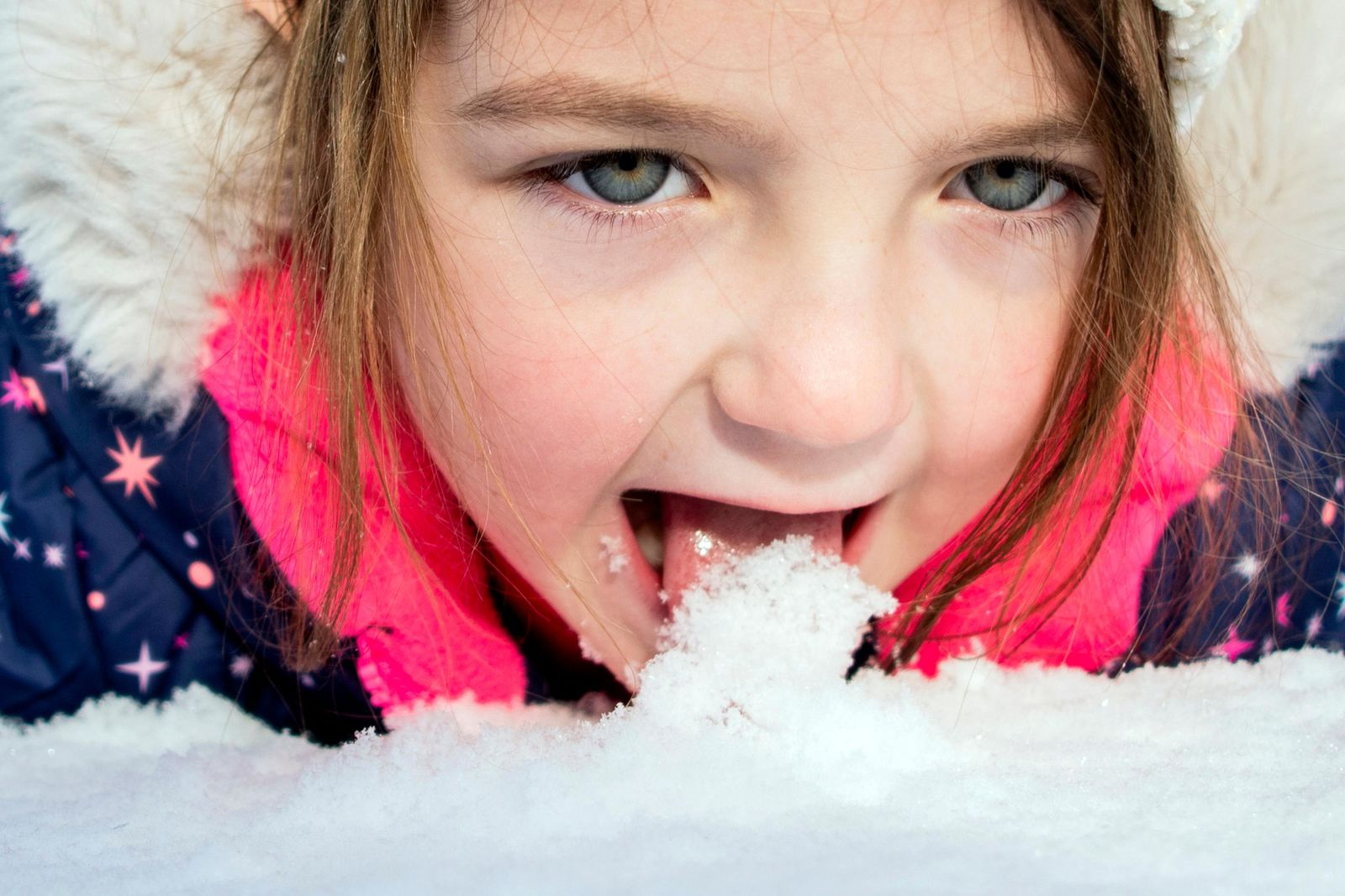 Emma Hart, 5 of Clio, stops to lick up fresh snow as she rolls around while sledding with her father Ryan Hart on the hill behind Southwestern Classical Academy on Tuesday, Nov. 12, 2019 in Flint, Mich. (Jake May/The Flint Journal via AP)