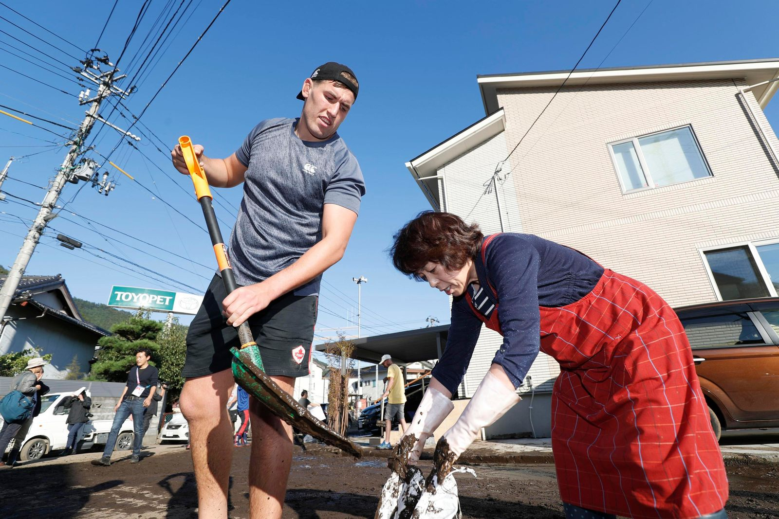 In this Oct. 13, 2019, photo, Canadian rugby player Josh Larsen, left, helps a resident to clean a road in Kamaishi, Iwate prefecture,  Japan, following the cancellation of their Rugby World Cup Pool B match against Namibia due to Typhoon Hagibis. The powerful typhoon unleashed torrents of rain and strong winds Saturday that left thousands of homes on Japan's main island flooded, damaged or without power. (Kyodo News via AP)