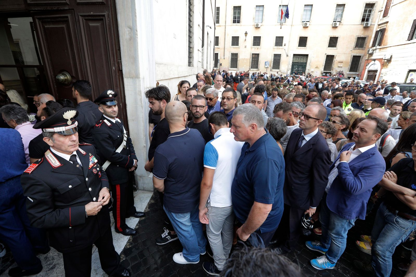 People arrive to pay respect in the church where Carabinieri officer Mario Cerciello Rega was laid in state, in Rome, Sunday, July 28, 2019. In a statement Saturday, Carabinieri officers investigating the death of Cerciello Rega, 35, said two young American tourists have been detained for alleged murder and attempted extortion. (AP Photo/Andrew Medichini)