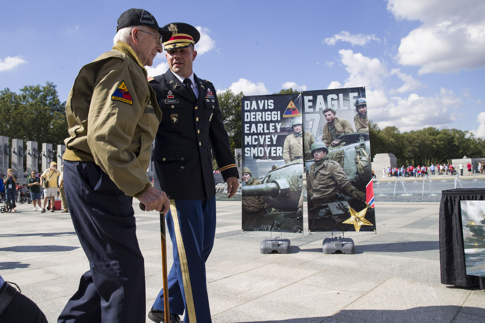 World War II veteran Clarence Smoyer, 96, left, walks to receives the Bronze Star from U.S. Army Maj. Peter Semanoff, right, at the World War II Memorial, Wednesday, Sept. 18, 2019, in Washington. (AP Photo/Alex Brandon)