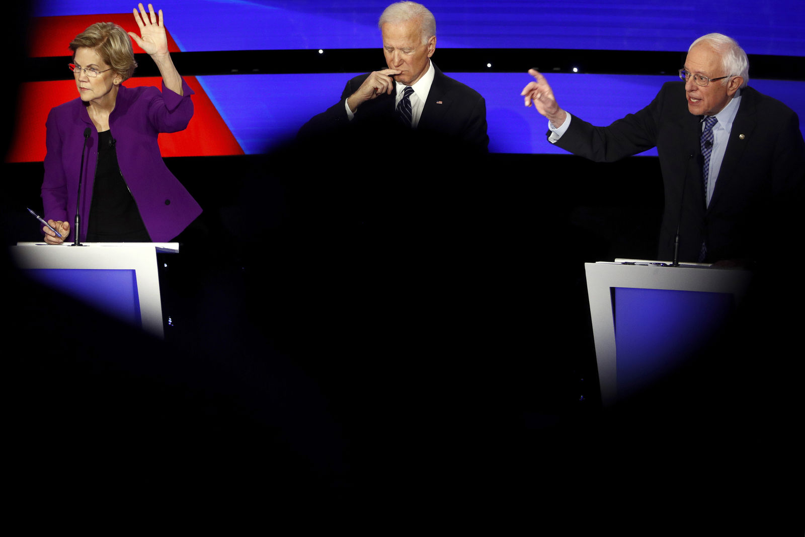 FILE - In this Jan. 14, 2020, file photo Democratic presidential candidate Sen. Elizabeth Warren, D-Mass., and Sen. Bernie Sanders, I-Vt., raise their hands to answer a question as Joe Biden pauses during a Democratic presidential primary debate hosted by CNN and the Des Moines Register in Des Moines, Iowa. Biden's juggling of the left wing along with mainstream Democrats and independents and Republicans disgruntled with Trump could end up as an unsuccessful attempt to be all things to all people. (AP Photo/Patrick Semansky, File)