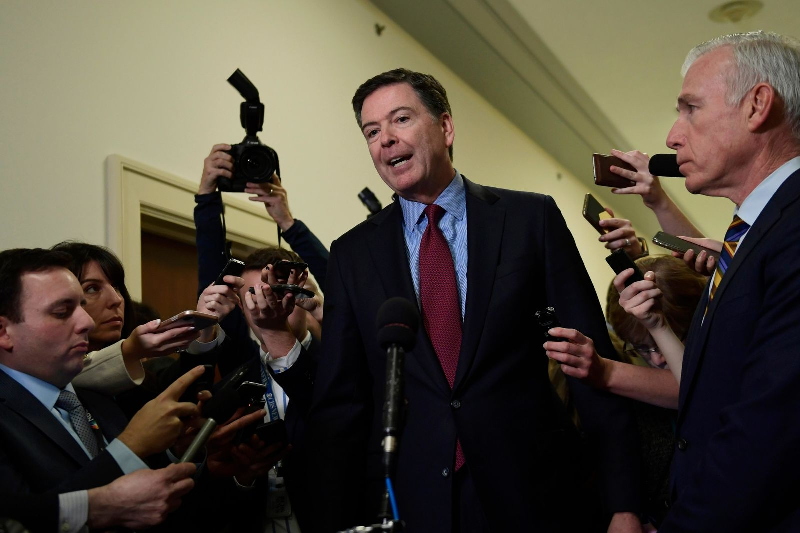 FILE – Former FBI Director James Comey, center, standing with his attornery David Kelley, right, speaks to reporters on Capitol Hill in Washington, Friday, Dec. 7, 2018, following his appearance before a closed-door hearing with the House Judiciary and House Oversight committees. (AP Photo/Susan Walsh)