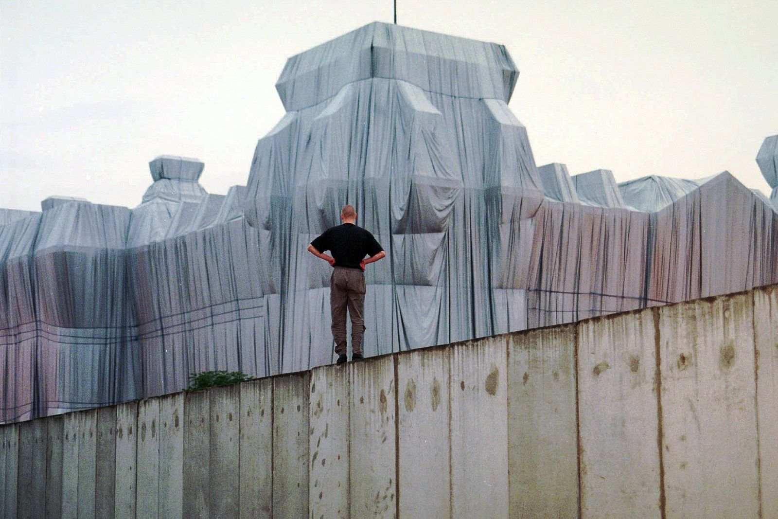 "FILE - In this June 22, 1995, file photo, a man stands at the top of remains of the Berlin Wall and looks at the wrapped Reichstag building, a project titled ""Wrapped Reichstag"" by American artist Christo and his wife Jeanne-Claude. (AP Photo/Jan Bauer, File)"
