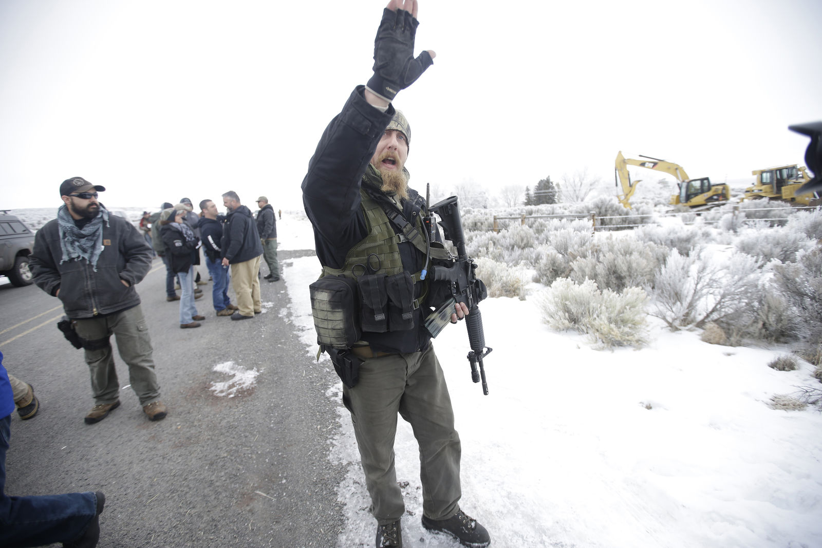 "A man standing guard pushes the media aside after members of the ""3% of Idaho"" group along with several other organizations arrived at the Malheur National Wildlife Refuge near Burns, Ore., on Saturday, Jan. 9, 2016. A small, armed group has been occupying the remote national wildlife refuge in Oregon for a week to protest federal land use policies. (AP Photo/Rick Bowmer)"