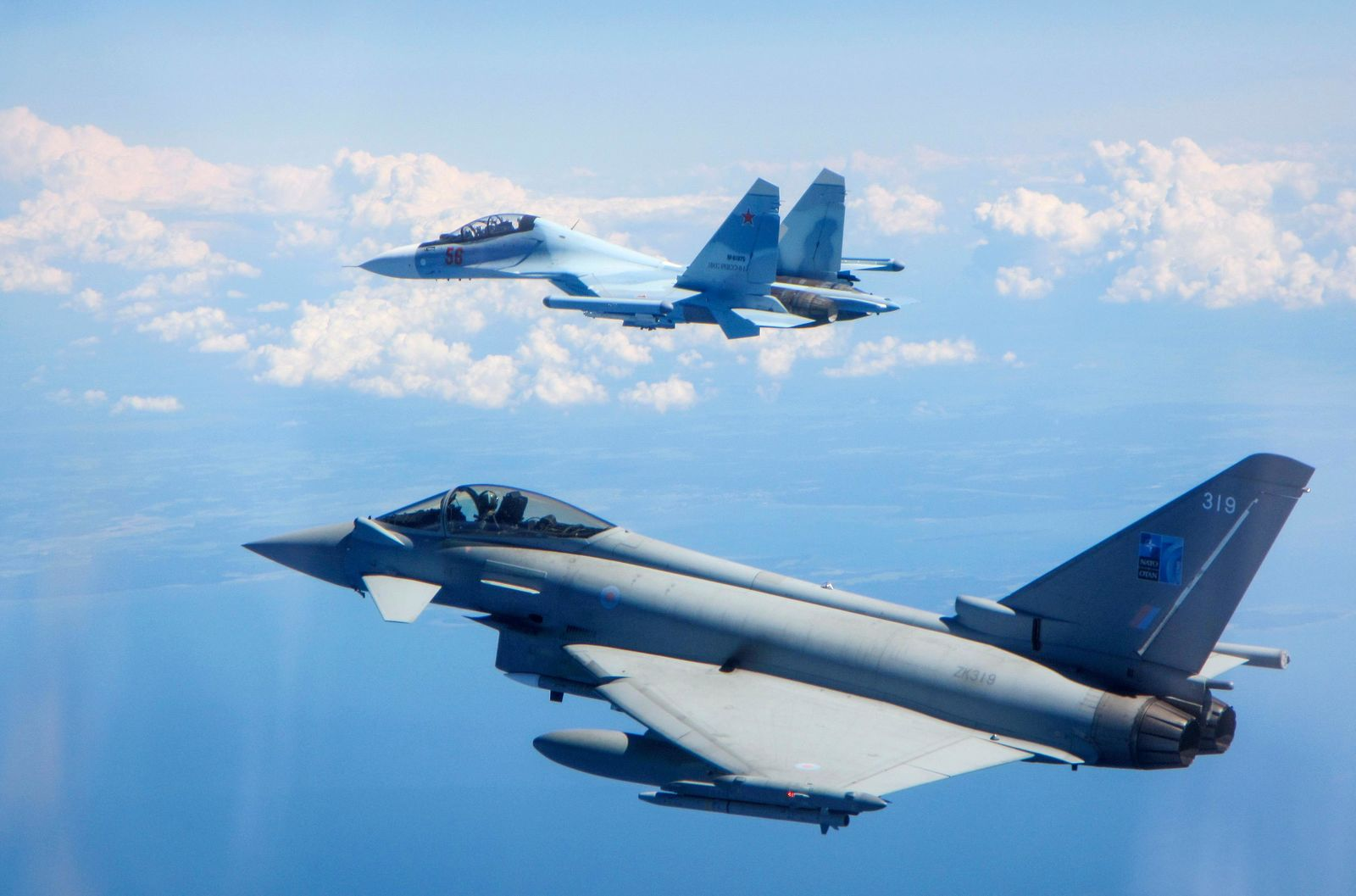 CAPTION CORRECTS AIRCRAFT NAME - In this photo  taken on Saturday, June 15, 2019, a Royal Air Force Typhoon jet, bottom, flies by a Su-30 Flanker fighter.{ } (UK Ministry of Defence via AP)