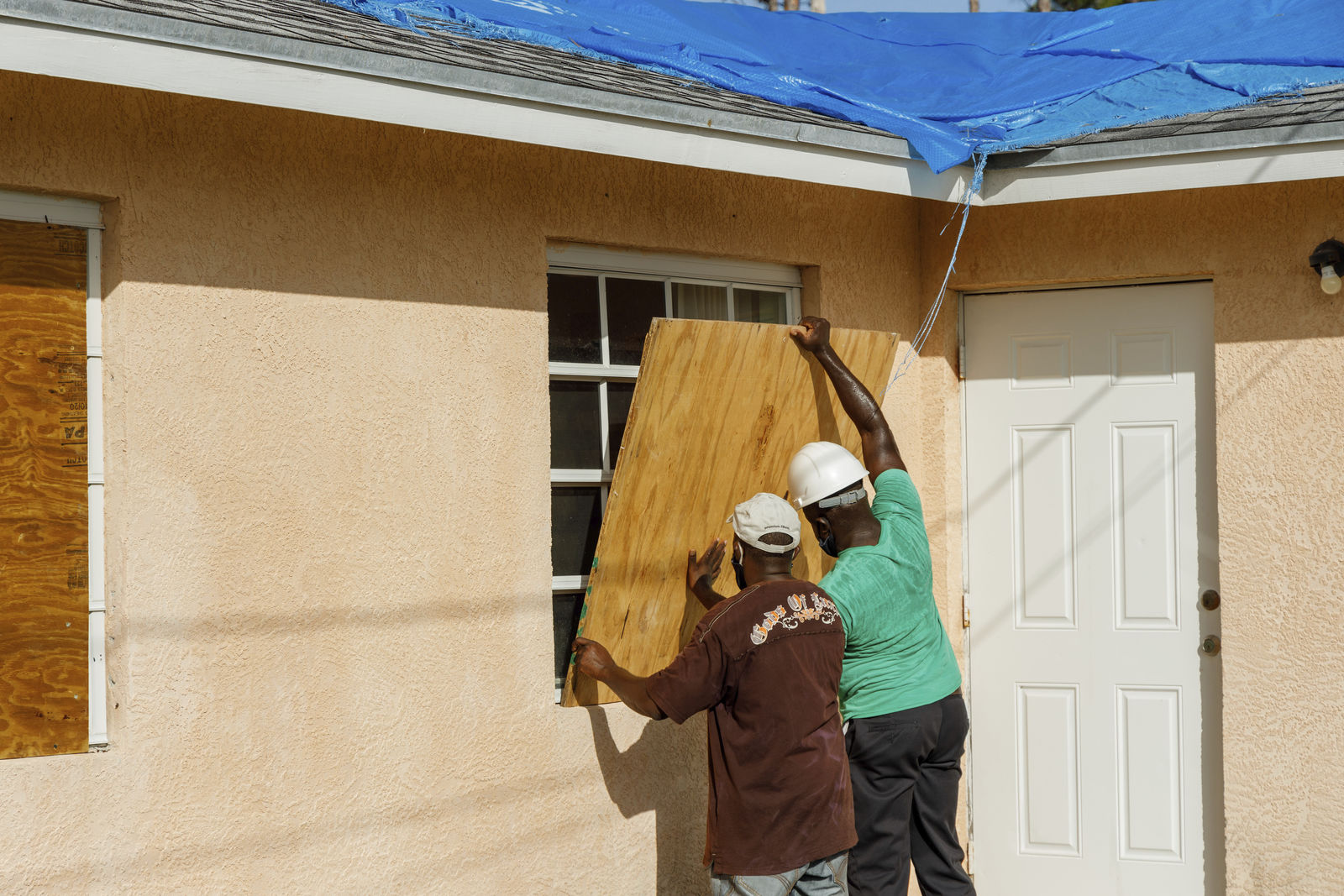 Residents cover a window with plywood in preparation for the arrival of Hurricane Isaias, in the Heritage neighborhood of Freeport, Grand Bahama, Bahamas, Friday, July 31, 2020. (AP Photo/Tim Aylen)