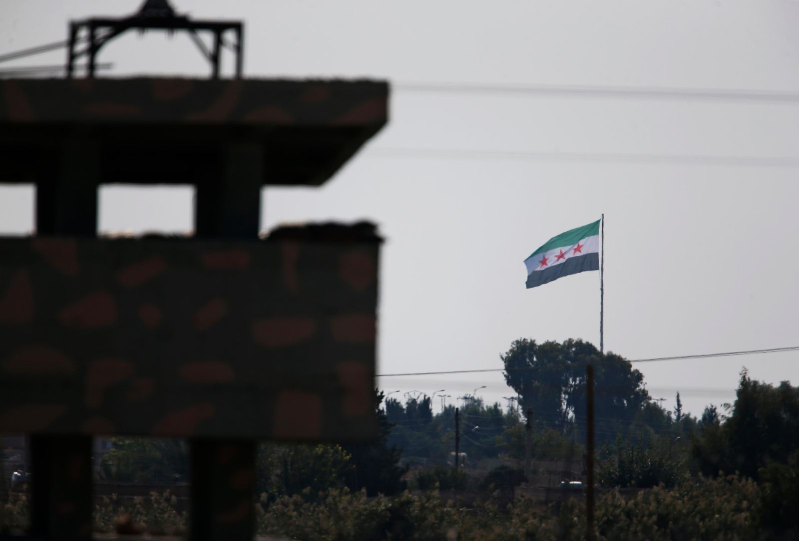 Syria's opposition flag flies on a pole in Tal Abyad, Syria, as seen from the town of Akcakale, Sanliurfa province, southeastern Turkey, Monday, Oct. 21, 2019. Turkey's President Recep Tayyip Erdogan is scheduled to meet Tuesday with Russian leader Vladimir Putin and the conflict between Turkey and the Kurds is expected to be the focus of their discussions. (AP Photo/Lefteris Pitarakis)