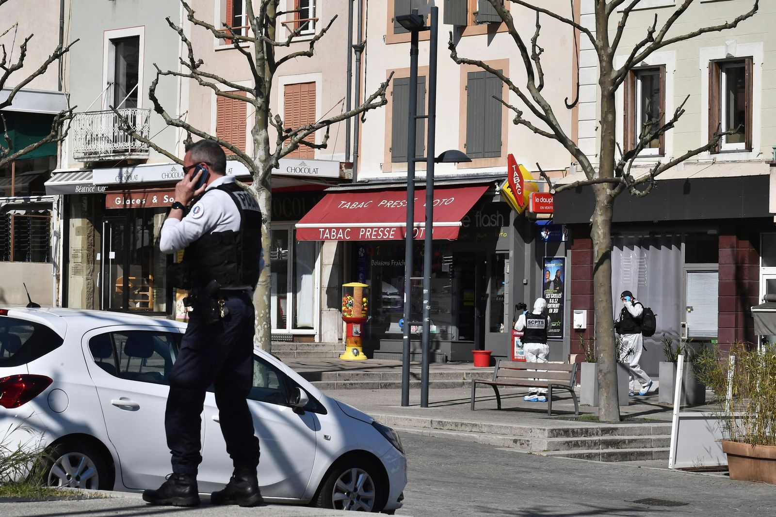 A police officer gives a phone call after a man wielding a knife attacked residents venturing out to shop in the town under lockdown, Saturday April 4, 2020 in Romans-sur-Isere, southern France. (AP Photo)