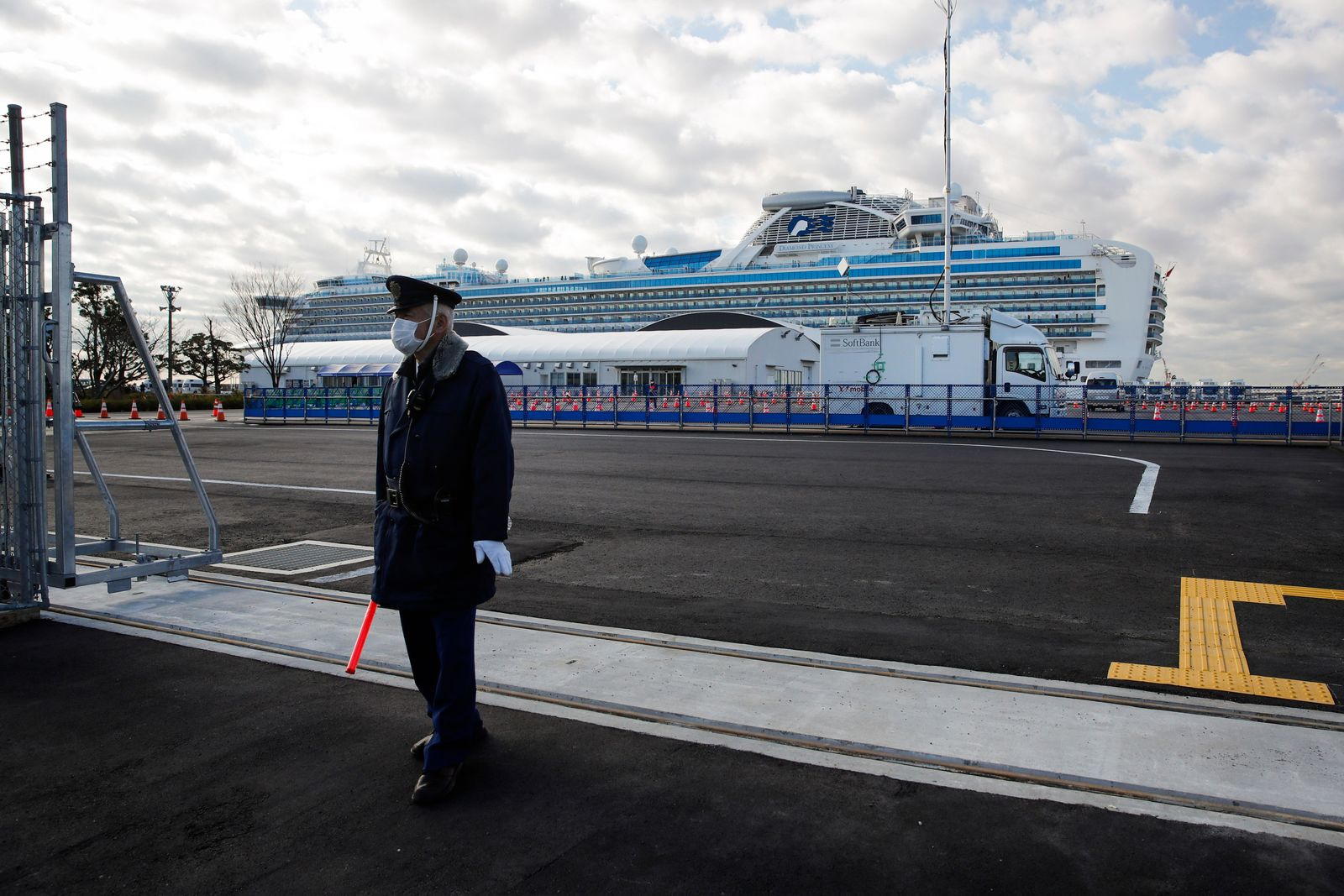 A security guard stands at the entrance to Yokohama port as the quarantined Diamond Princess cruise ship is seen in the background Wednesday, Feb. 19, 2020, in Yokohama, near Tokyo. Passengers tested negative for COVID-19 will start disembarking Wednesday. (AP Photo/Jae C. Hong)