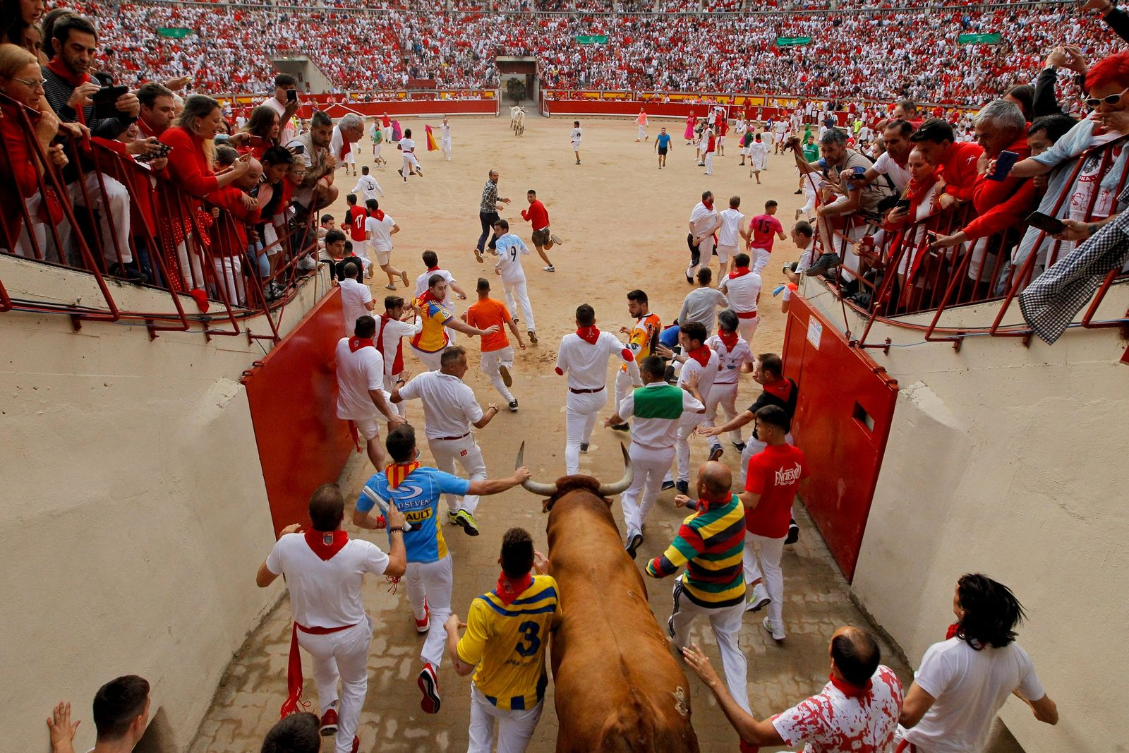 "Revellers and a fighting bull arrive at the bullring during the running of the bulls at the San Fermin Festival, in Pamplona, northern Spain, Sunday, July 14, 2019. The San Fermin fiesta made internationally famous by Ernest Hemingway in his novel ""The Sun Also Rises"" draws around 1 million partygoers each year.(AP Photo/Alvaro Barrientos)"
