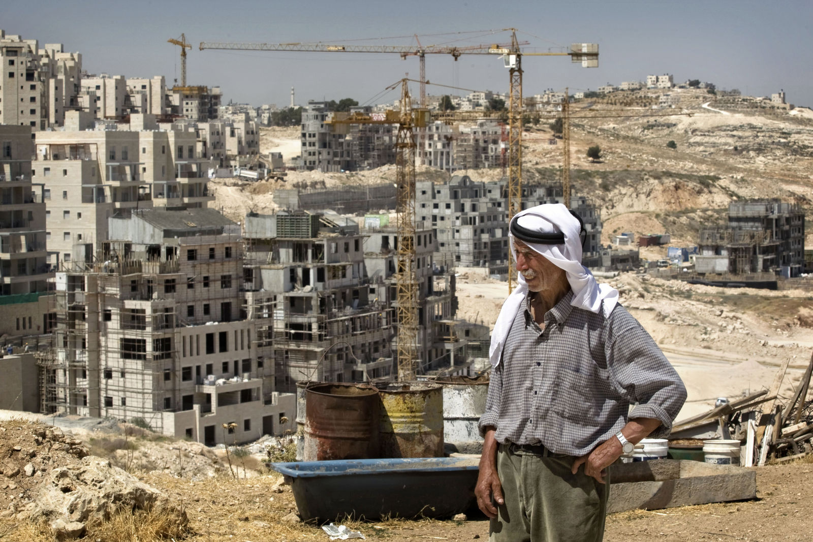 FILE - In this June 3, 2009 file photo, Palestinian Said Eid stands next to his house, not seen, as construction continues on a new housing development in the Jewish neighborhood of Har Homa in east Jerusalem, background.{ } (AP Photo/Sebastian Scheiner, File)