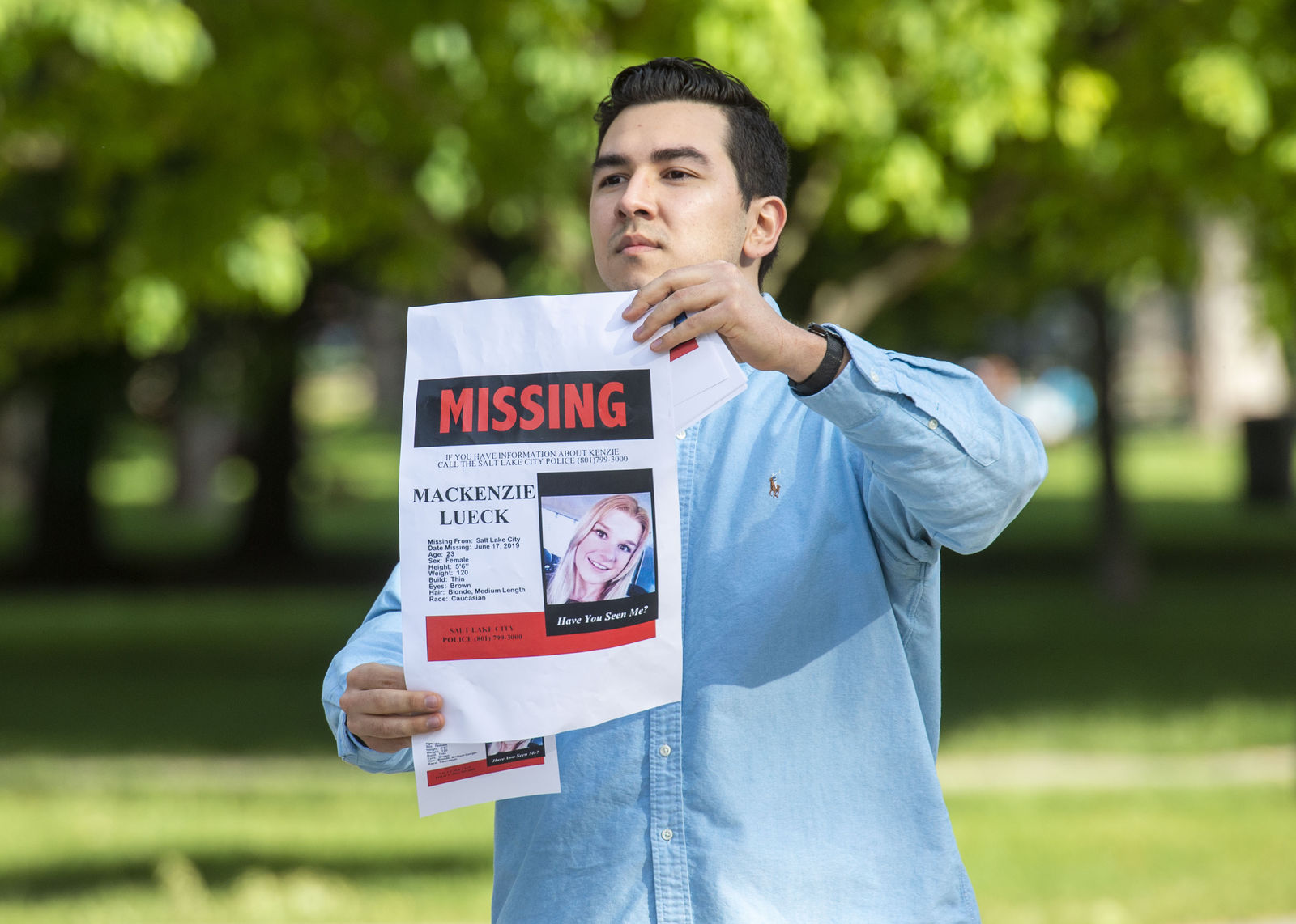 In this Saturday, June 22, 2019 photo, Nate Crispo holds a holds a sign with Mackenzie Lueck's photo in Liberty Park in Salt Lake City. Police and friends are investigating the disappearance of the 23-year-old University of Utah student, whose last communication with her family said she arrived at Salt Lake City International Airport on Monday, June 17. (Rick Egan/The Salt Lake Tribune via AP)