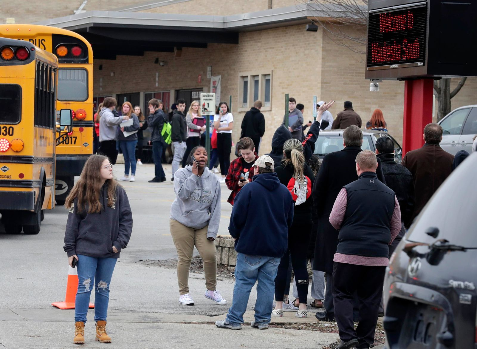 Waukesha South High School students find their waiting parents and friends and hug after they leave the building following shots fired inside the school, Monday, December 2, 2019. (Rick Wood/Milwaukee Journal-Sentinel via AP)