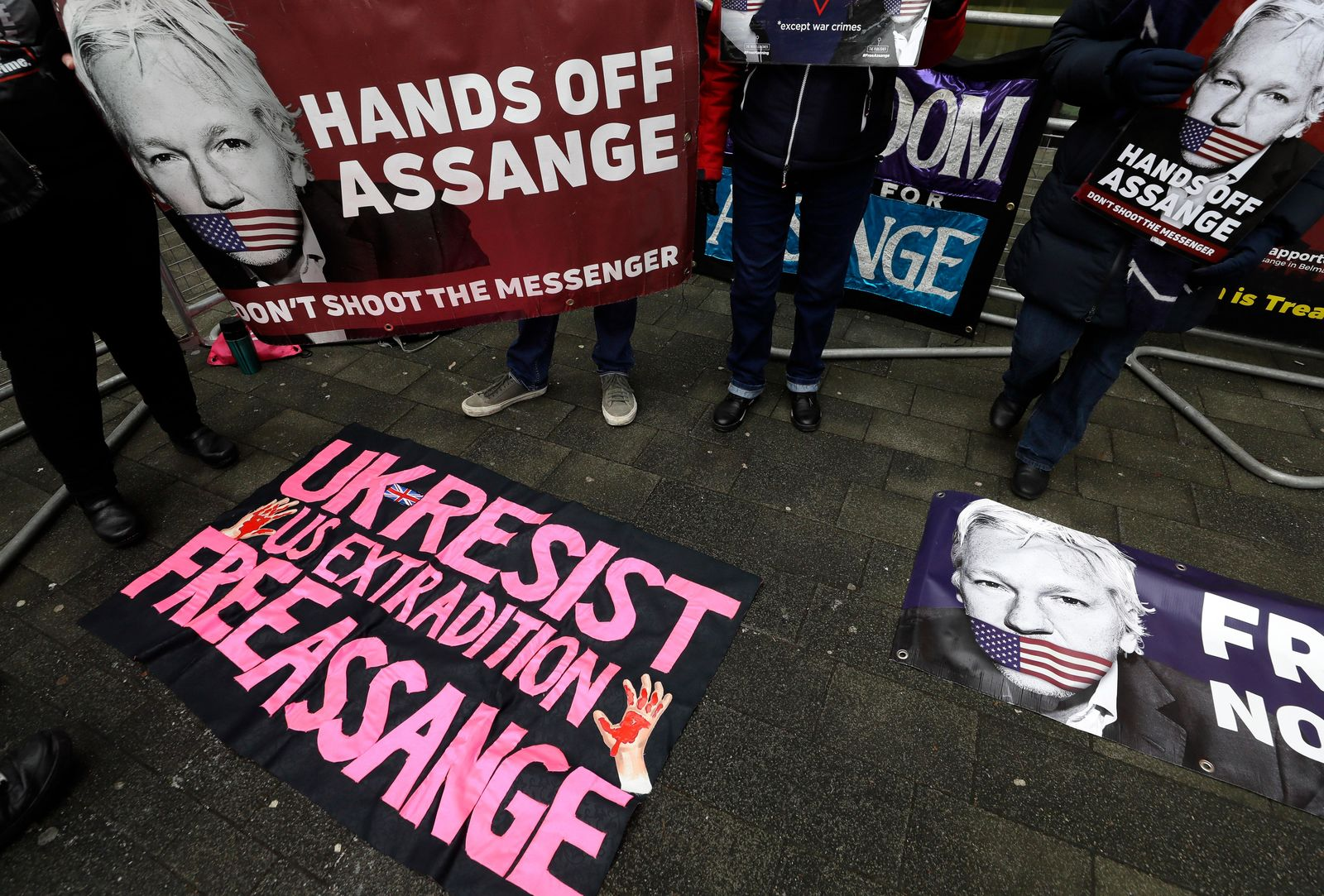 Demonstrators supporting Julian Assange hold banners outside Westminster Magistrates Court in London, Thursday, Jan. 23, 2020. (AP Photo/Kirsty Wigglesworth)