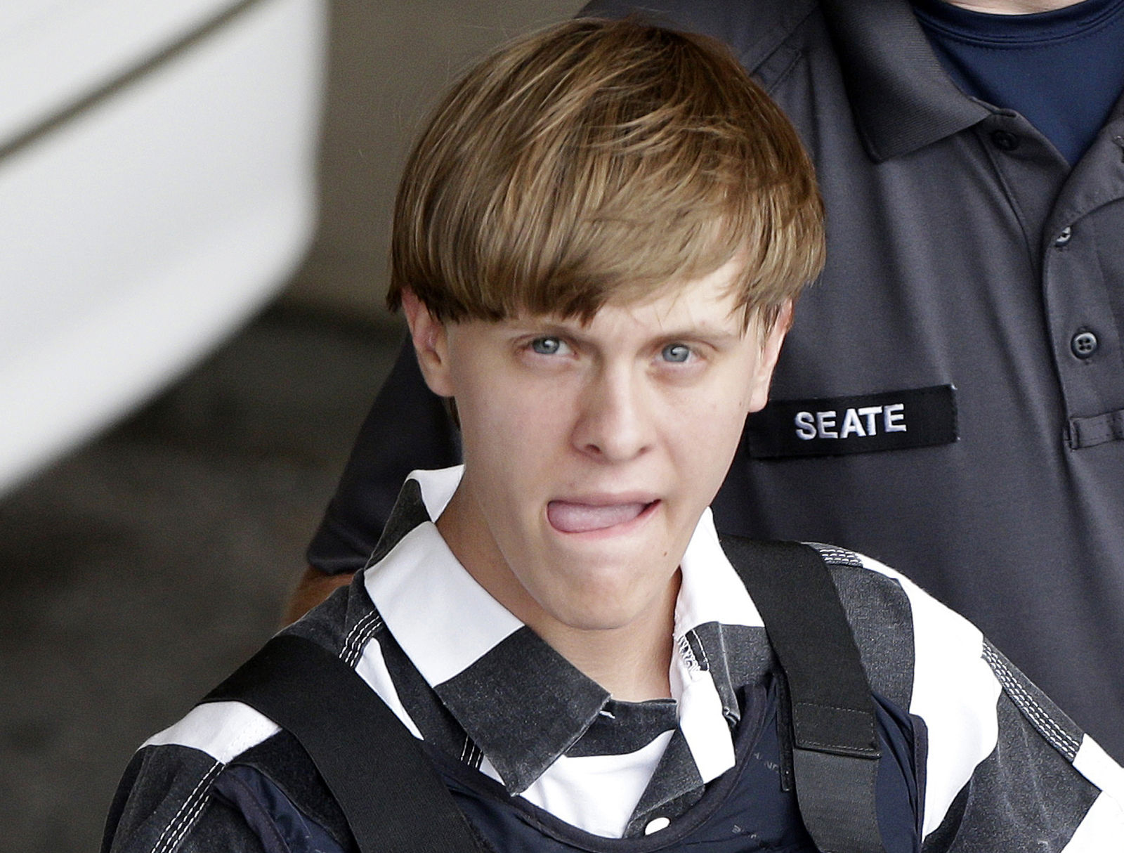 FILE - In this June 18, 2015, file photo, Charleston, S.C., shooting suspect Dylann Storm Roof is escorted from the Cleveland County Courthouse in Shelby, N.C. A federal appeals court has reinstated a lawsuit over a faulty background check that allowed Roof to buy the gun he used to kill nine people in a racist attack at a South Carolina church. A three-judge panel of the 4th U.S. Circuit Court of Appeals on Friday, Aug. 30, 2019, reversed a lower court judge who threw out the lawsuit brought by survivors and relatives of people killed in the 2015 massacre at Charleston's AME Emanuel Church. (AP Photo/Chuck Burton, File)