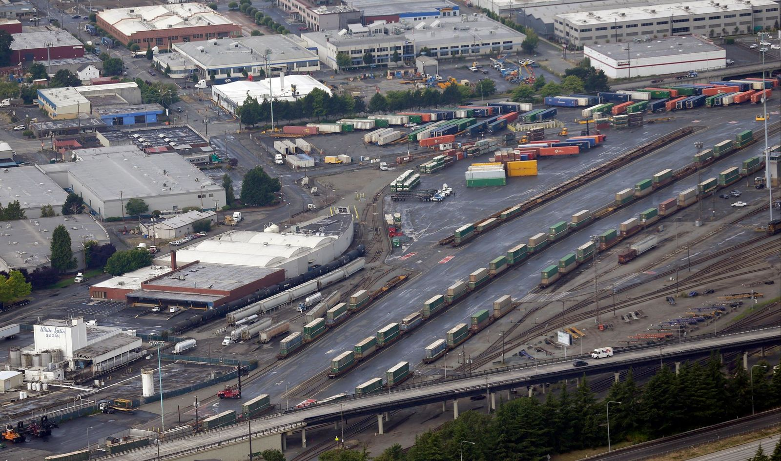 In this Aug. 2, 2014 aerial photo, trains with cargo containers are shown south of Seattle. More than two dozen major companies ranging from Campbell Soup to Kia filed anti-trust lawsuits on Sept. 30, 2019 against the nation's four largest railway companies, contending the railroads had a price-fixing scheme to illegally boost profits. (AP Photo/Ted S. Warren)