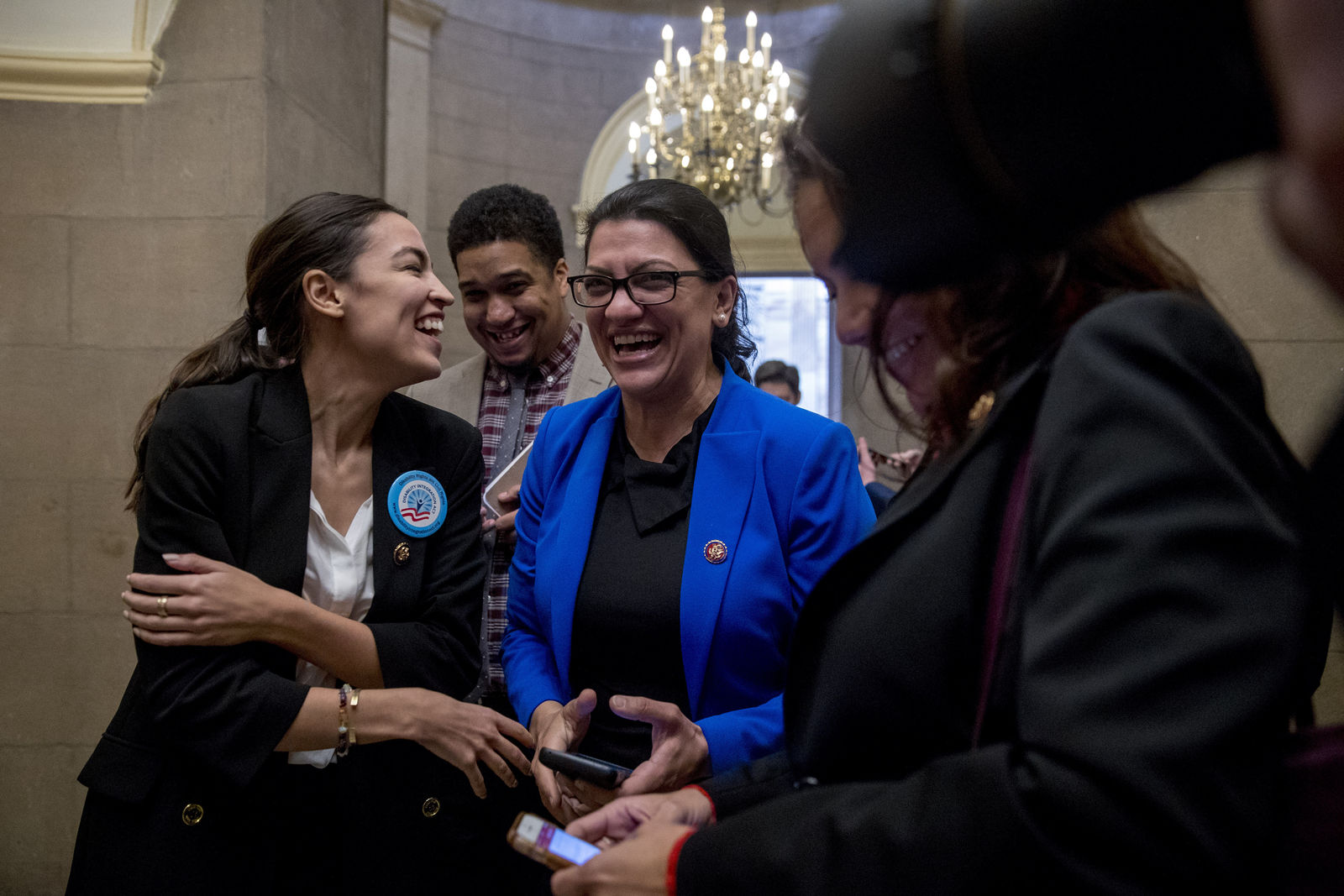 Rep. Alexandria Ocasio-Cortez, D-N.Y., left, and Rep. Rashida Tlaib, D-Mich., right, laugh as they wait for other freshman Congressmen to deliver a letter calling to an end to the government shutdown to deliver to the office of Senate Majority Leader Mitch McConnell of Ky., on Capitol Hill in Washington, Wednesday, Jan. 16, 2019. Also pictured is Rep. Veronica Escobar, D-Texas, right. (AP Photo/Andrew Harnik)