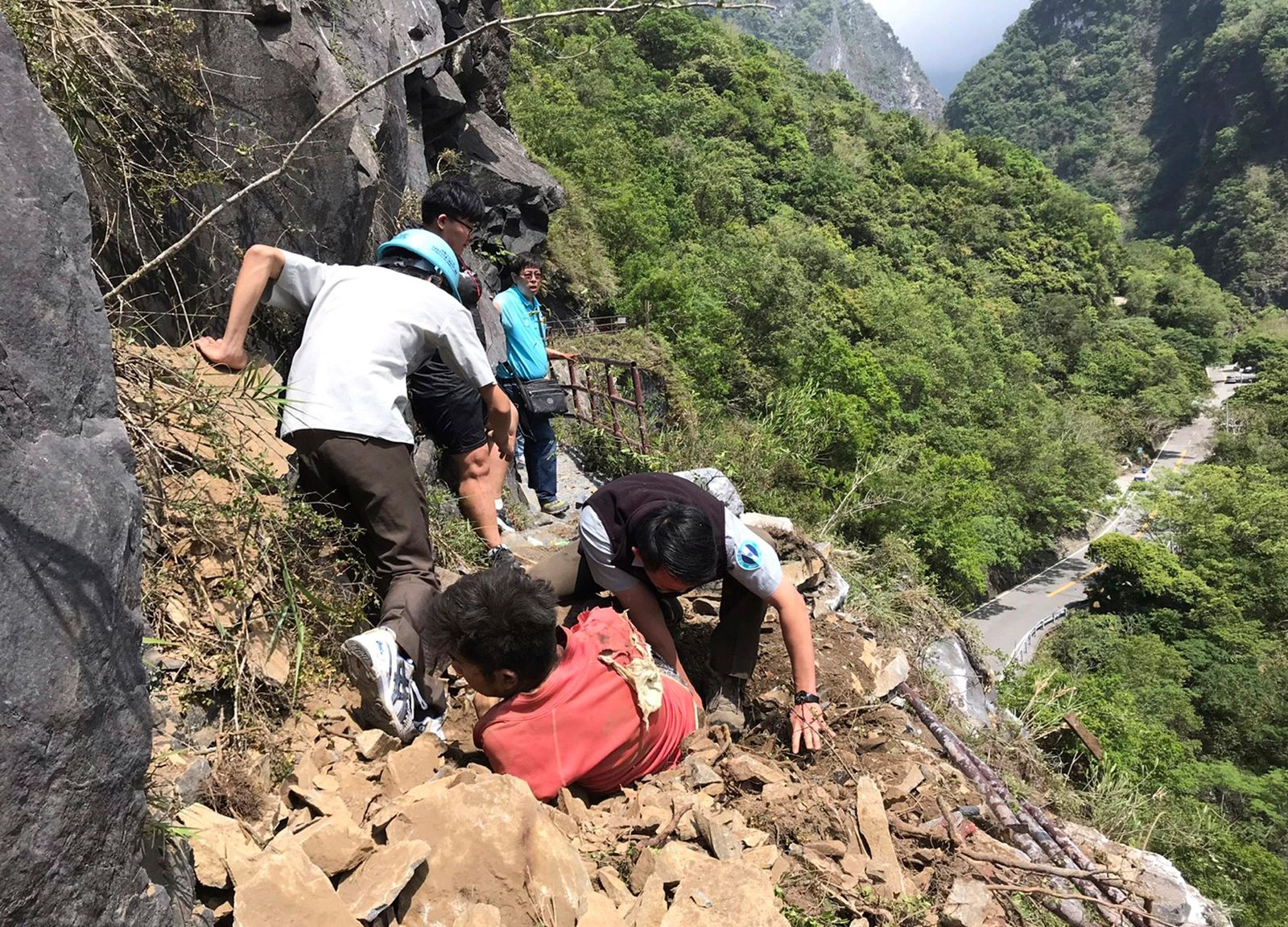 In this photo released by Taroko National Park, an injured Malaysian tourist, in red, is assisted by rescue workers at the Taroko National Park in Hualien in eastern Taiwan Thursday, April 18, 2019.. (Taroko National Park via AP)