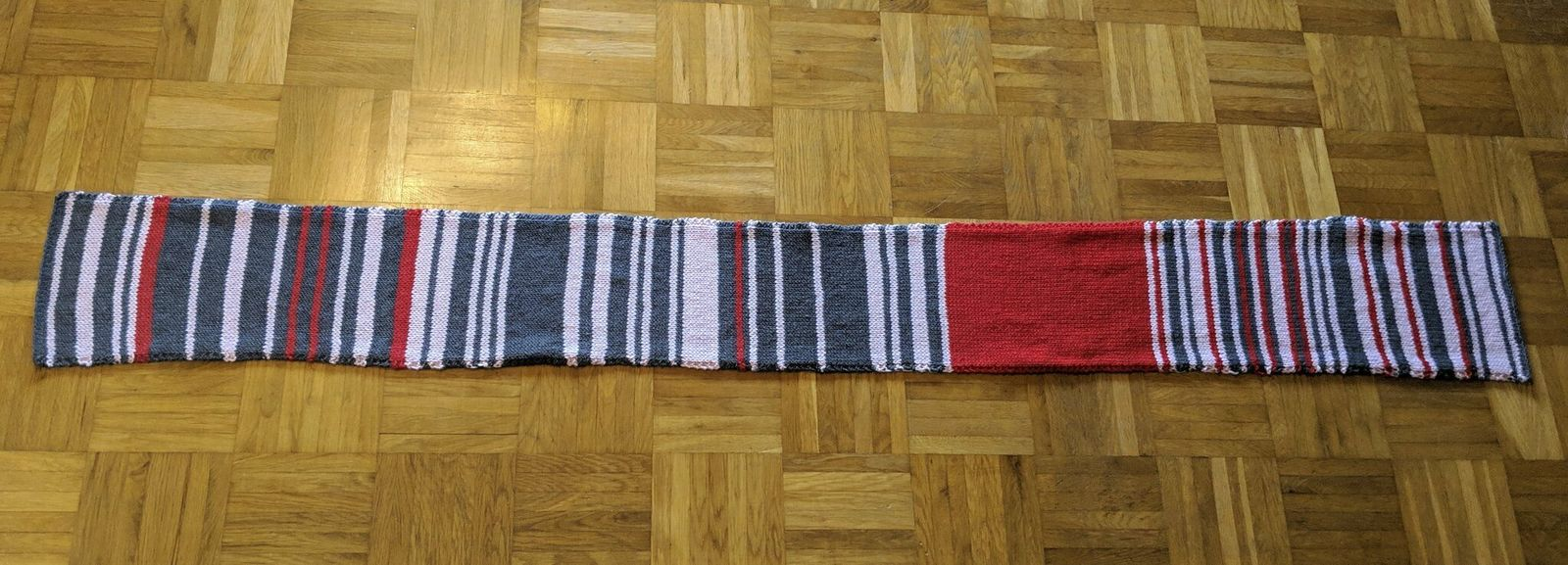 This undated photo made available Thursday Jan. 17, 2019, shows the so called 'delay scarf' which a Munich commuter has knitted with each colour reflecting the amount of time her journey with Deutsche Bahn train service had been delayed. (Sara Weber via AP)