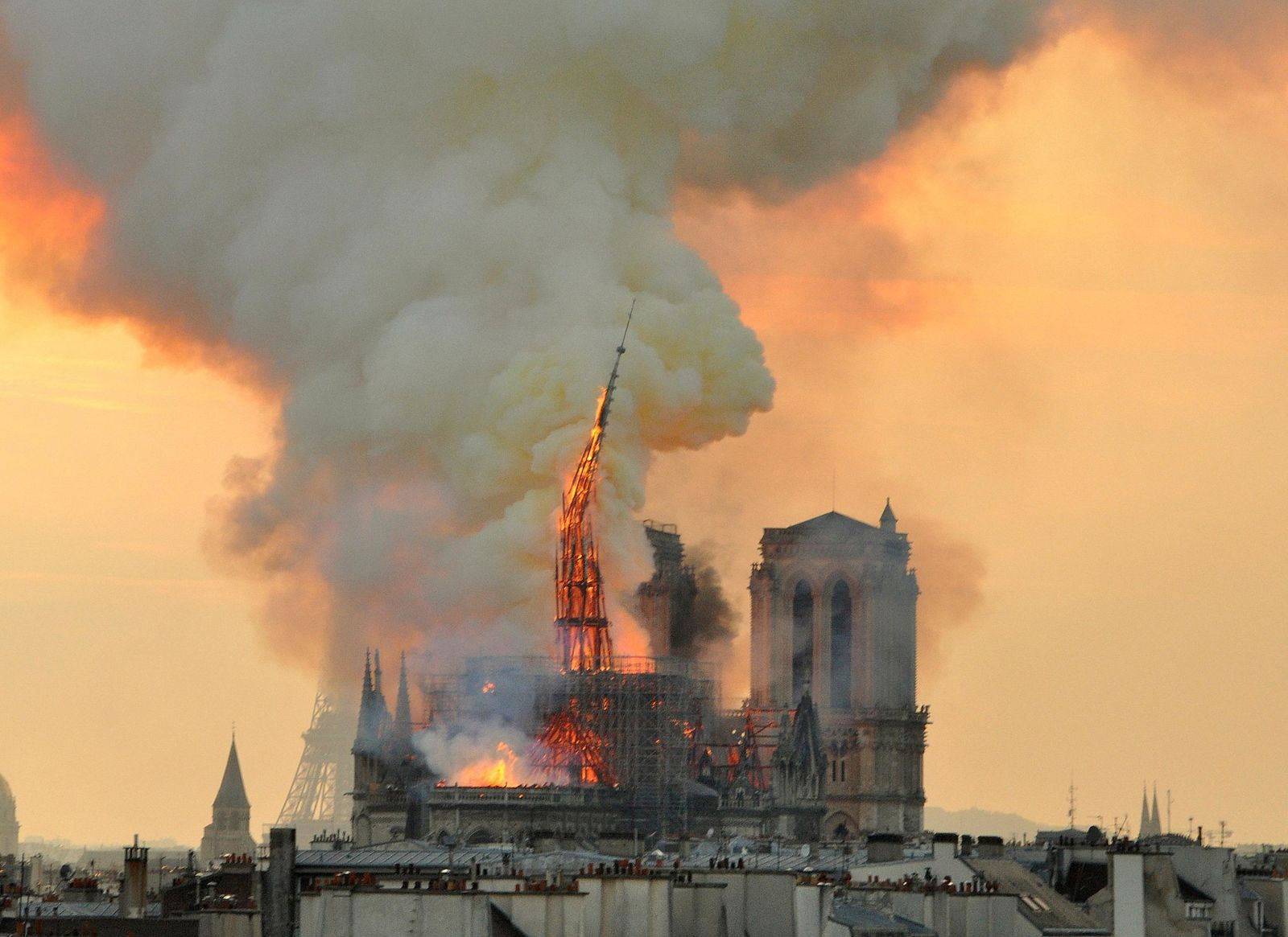 In this image made available on Tuesday April 16, 2019 flames and smoke rise from the blaze as the spire starts to topple on Notre Dame cathedral in Paris, Monday, April 15, 2019. (AP Photo/Thierry Mallet)