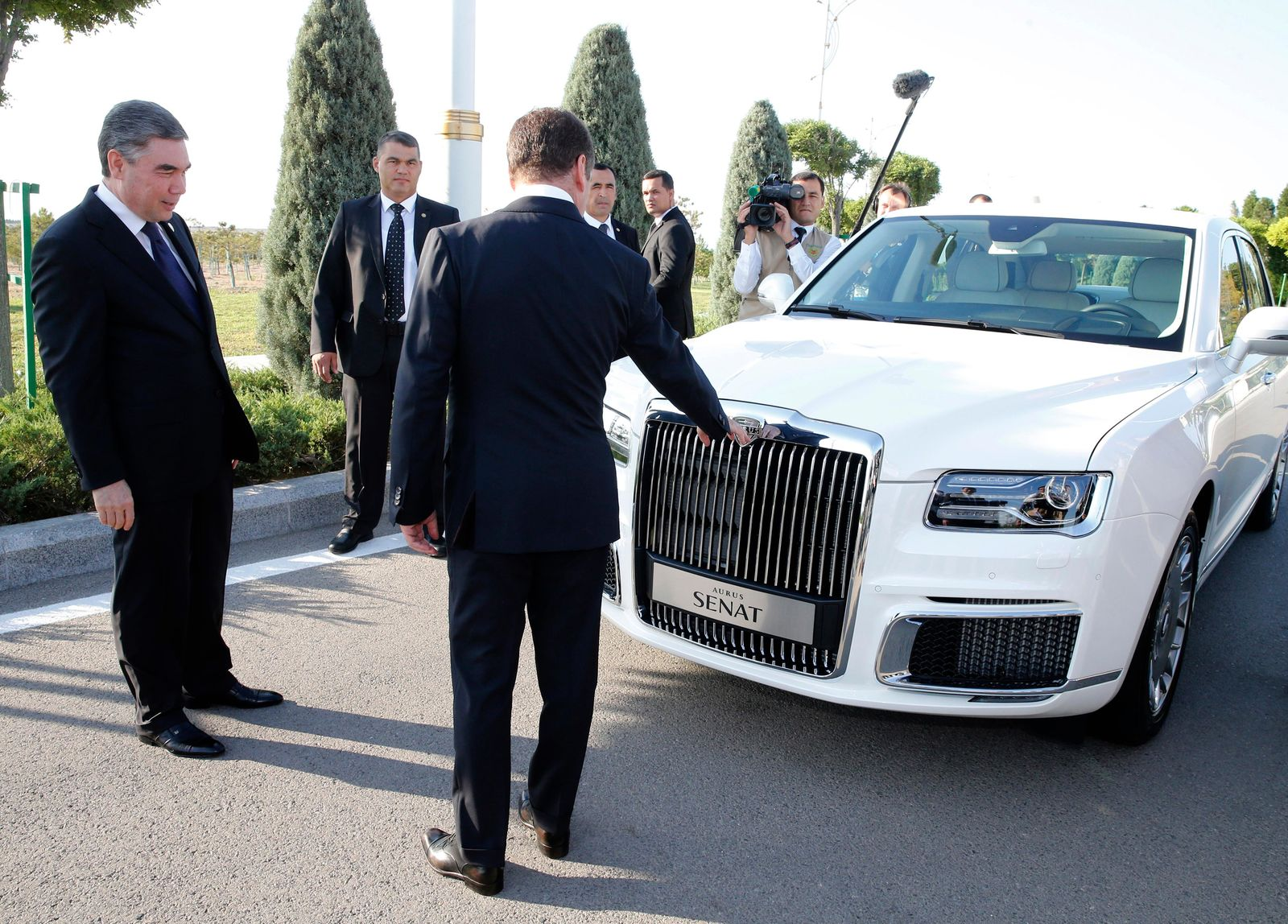 Russian Prime Minister Dmitry Medvedev, back to a camera, shows Turkmenistan's President Gurbanguly Berdymukhamedov a Russian made limousine Aurus Senat prior to a session of the First Caspian Economic Forum in Turkmenbashi, Turkmenistan, Monday, Aug. 12, 2019. (Dmitry Astakhov, Sputnik, Government Pool Photo via AP)