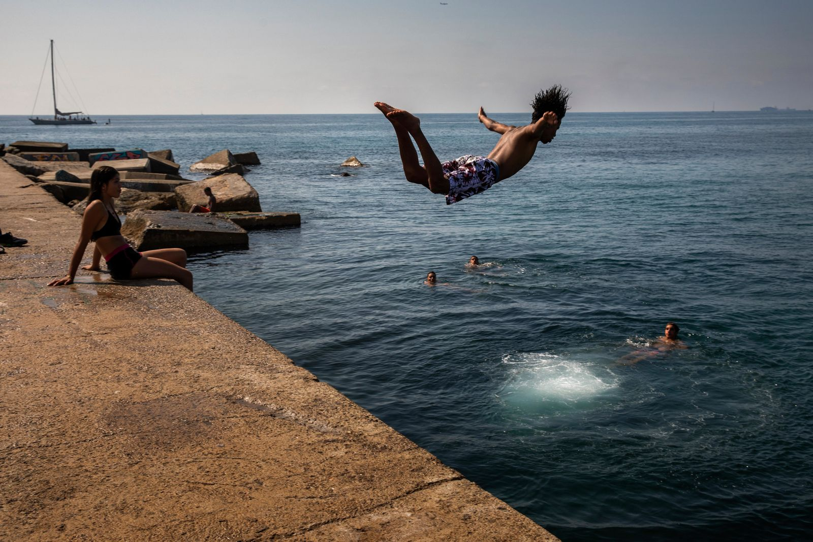 FILE - In this file photo dated Thursday, July 25, 2019, a boy jumps into the water at the beach in Barcelona, Spain. (AP Photo/Emilio Morenatti, FILE)