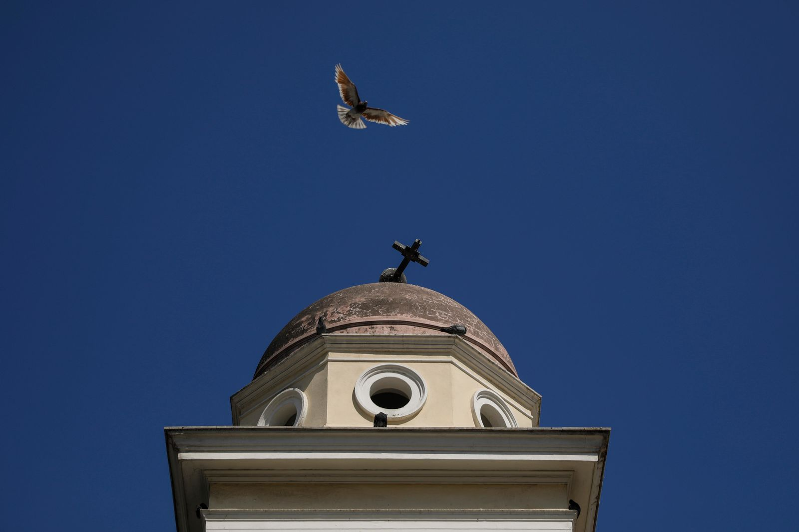 A pigeon flies next the damaged bell tower of Pantanassa church at the Monastiraki square following an earthquake in Athens, Friday, July 19, 2019. (AP Photo/Petros Giannakouris)