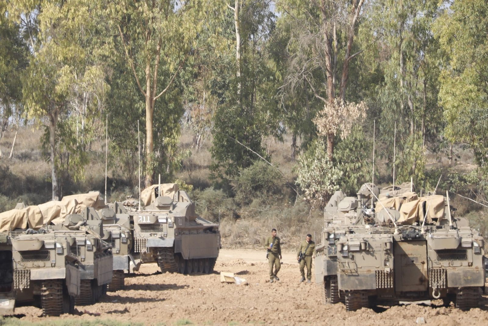 Israeli soldiers walk past military vehicles in a gathering point near the Israel-Gaza Border, Thursday, Nov. 14, 2019.{ } (AP Photo/Ariel Schalit)