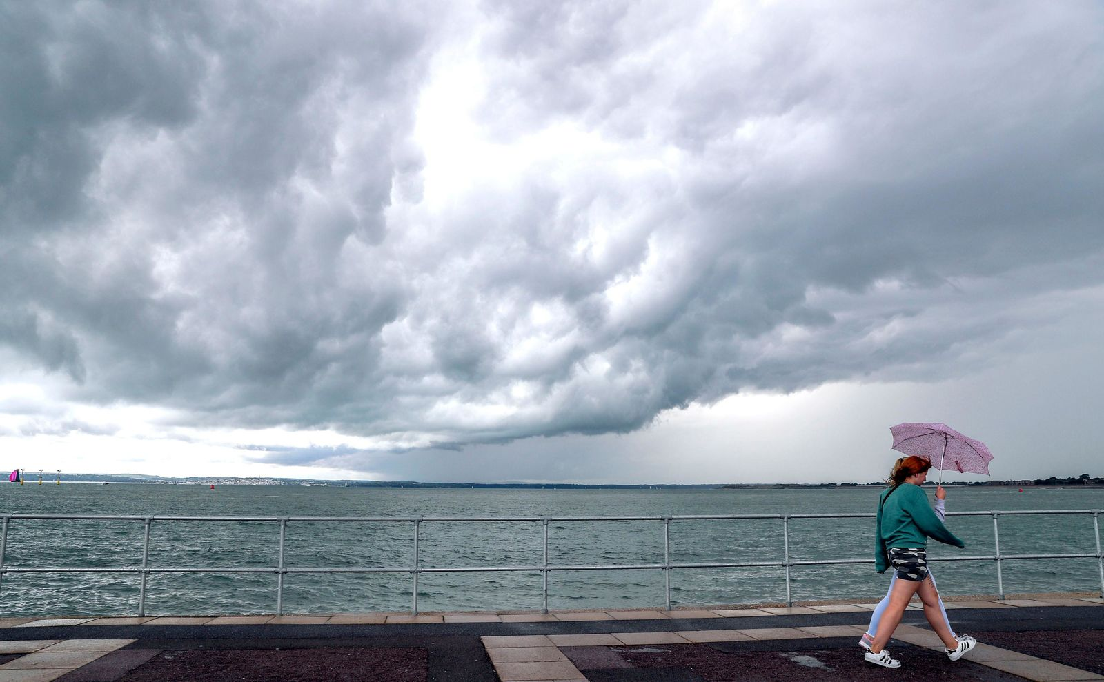 Women walk by the pier as rain clouds gather over the sea, in Southsea, Hampshire, England, Monday, Aug. 12, 2019. (Steve Parsons/PA via AP)