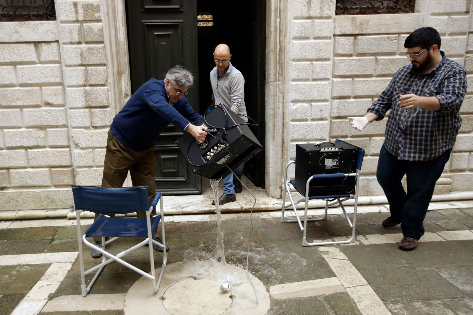A man empties electronic equipment from water in Venice, Italy, Saturday, Nov. 16, 2019. High tidal waters returned to Venice on Saturday, four days after the city experienced its worst flooding in 50 years. (AP Photo/Luca Bruno)