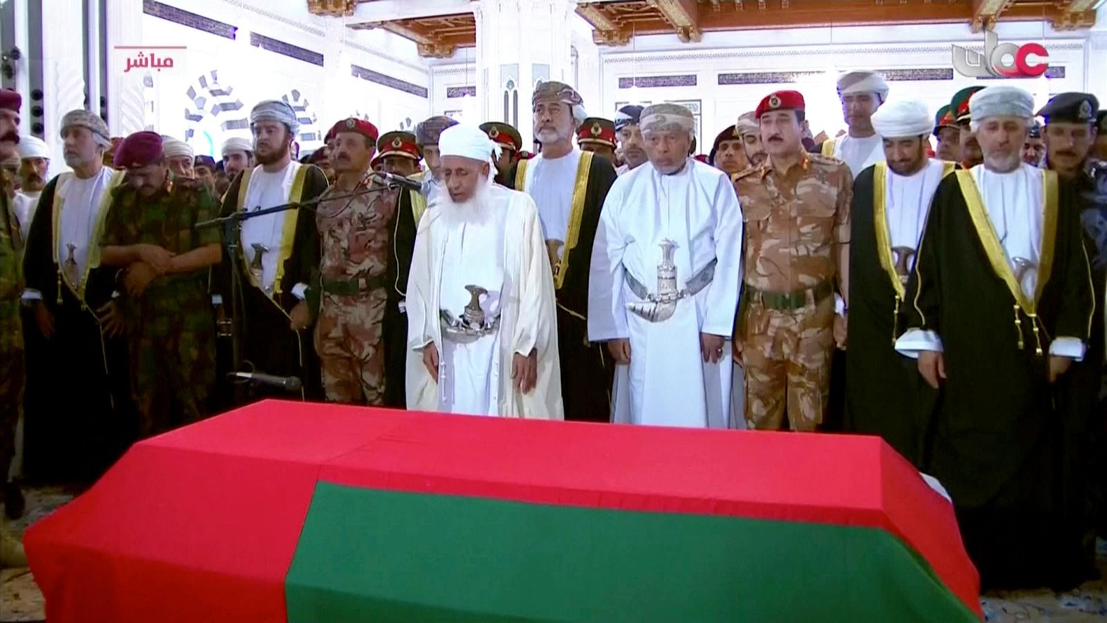 This image made from video shows Oman's new sultan Haitham bin Tariq Al Said, center between two men with daggers, attends the prayer ceremony over Sultan Qaboos coffin at Sultan Qaboos Grand Mosque in Muscat, Oman, Saturday, Jan. 11, 2020. Sultan Qaboos bin Said, the Mideast's longest-ruling monarch who seized power in a 1970 palace coup and pulled his Arabian sultanate into modernity while carefully balancing diplomatic ties between adversaries Iran and the U.S., has died. He was 79. (Oman TV via AP)