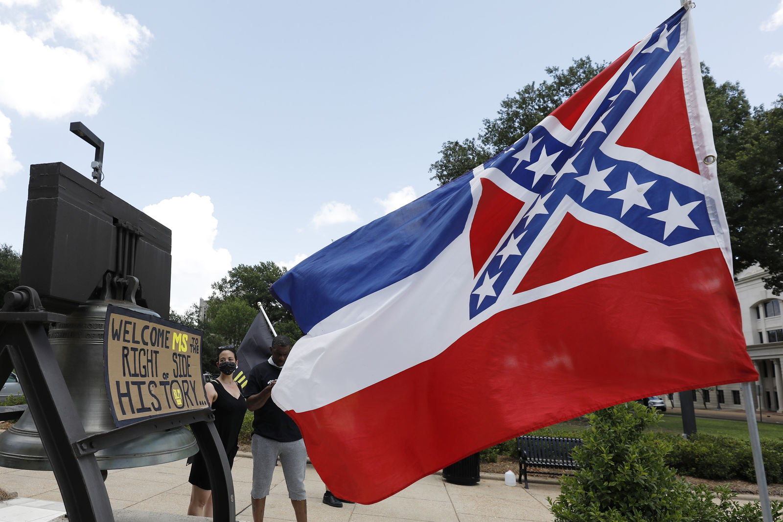 "A Mississippi state flag waves adjacent to a flag change supporter's sign that welcomes the state to ""the right side of history,"" outside the Capitol in Jackson, Miss., Sunday, June 28, 2020. (AP Photo/Rogelio V. Solis)"