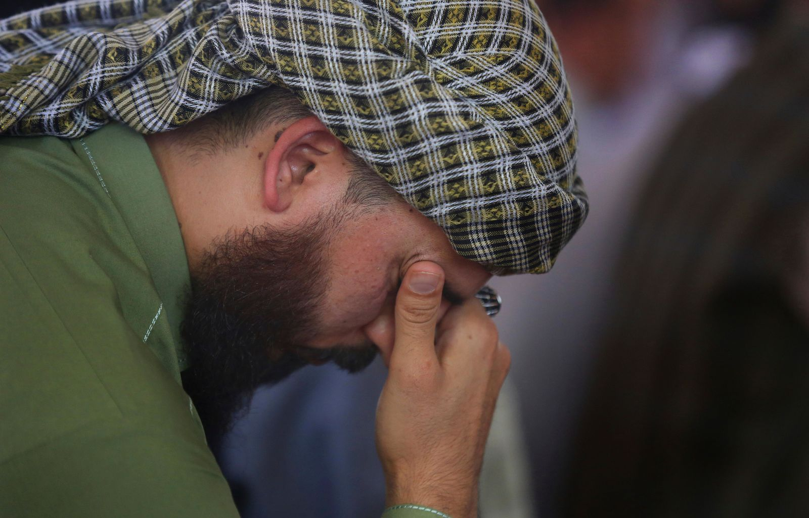 A man mourns for victims of the Dubai City wedding hall bombing during a memorial service at a mosque in Kabul, Afghanistan, Tuesday, Aug. 20, 2019. Hundreds of people have gathered in mosques in Afghanistan's capital for memorials for scores of people killed in a horrific suicide bombing at a Kabul wedding over the weekend. (AP Photo/Rafiq Maqbool)