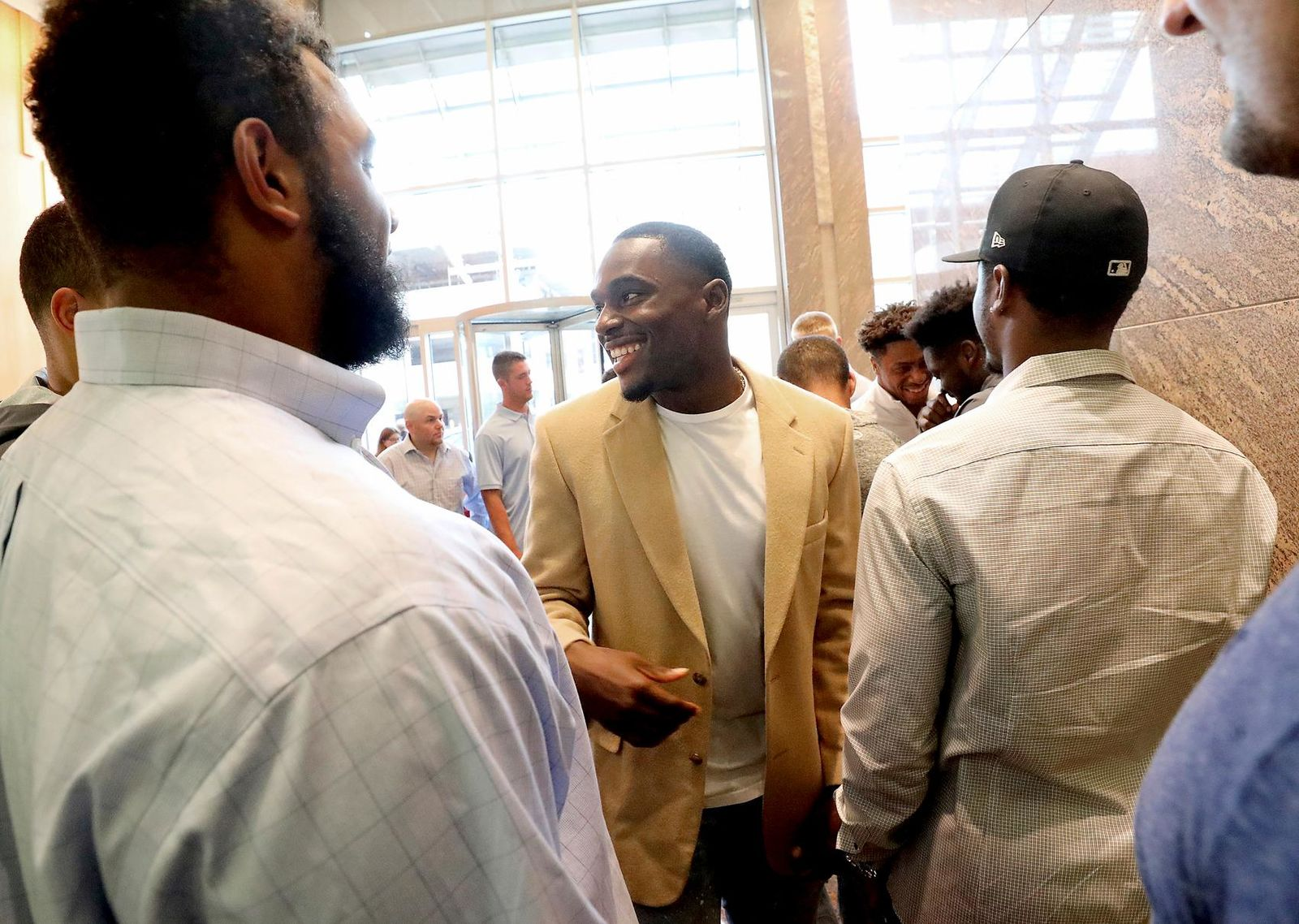Former Wisconsin Badger football player Quintez Cephus, center, greets current members of the team following a press conference to reiterated his request for reinstatement to the university in Madison, Wis. Monday, Aug. 12, 2019.{ } (John Hart/Wisconsin State Journal via AP)