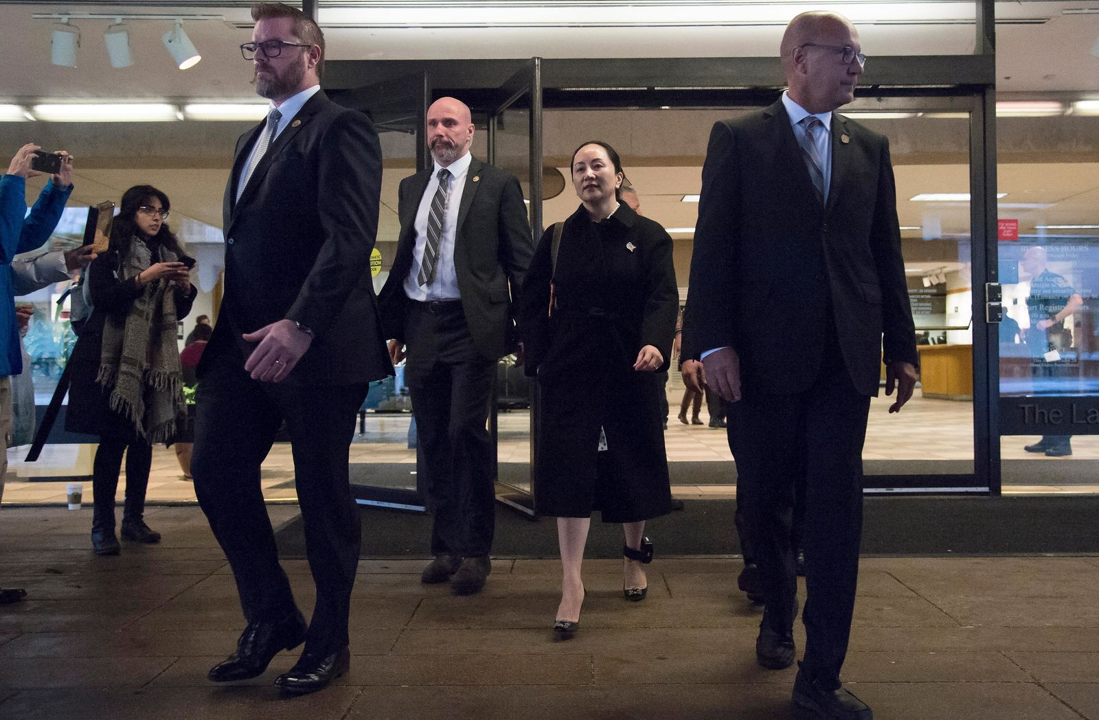 Meng Wanzhou, chief financial officer of Huawei, is flanked by security as she leaves B.C. Supreme Court in Vancouver, Thursday, January 23, 2020. (Jonathan Hayward/The Canadian Press via AP)
