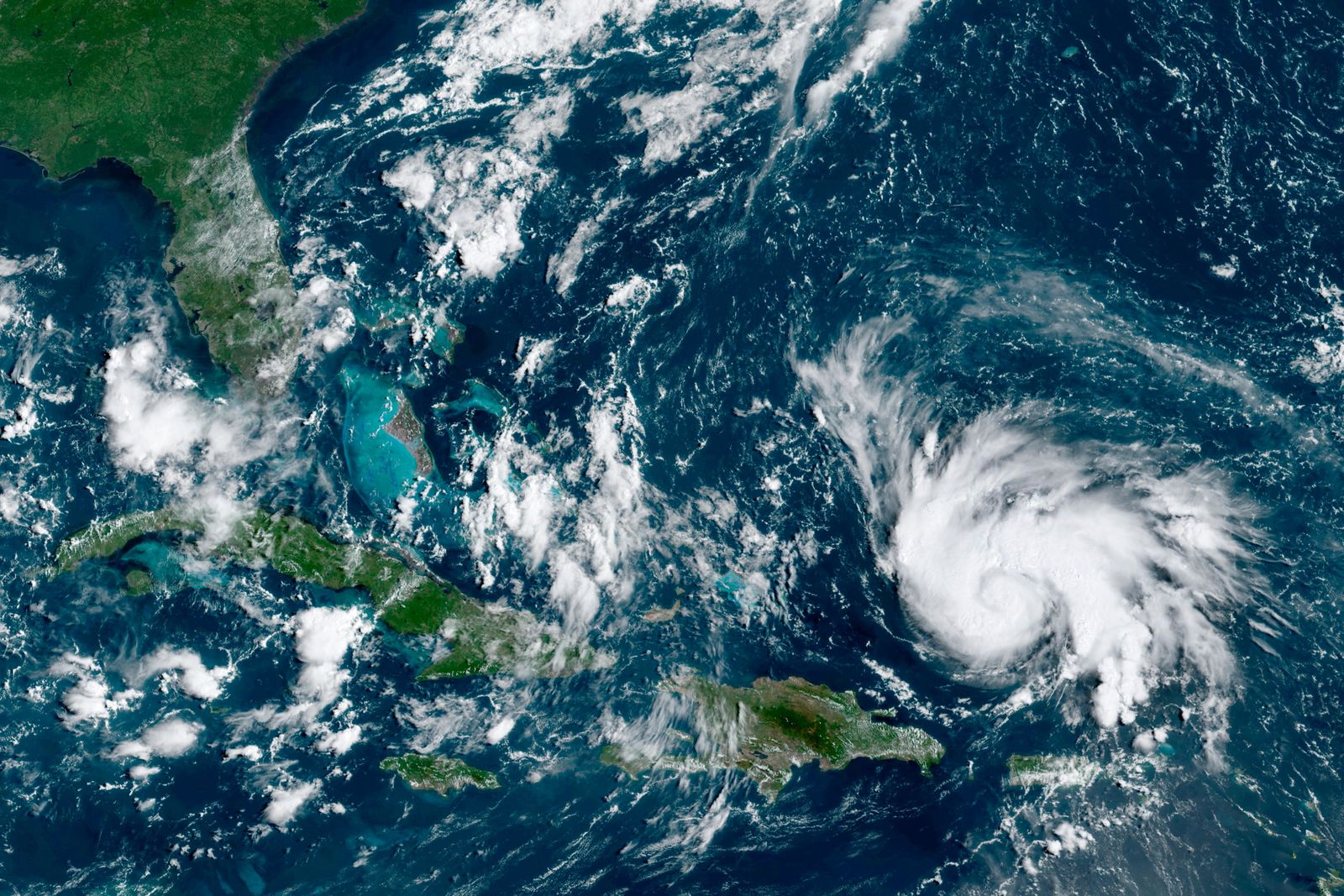 This GOES-16 satellite image taken Thursday, Aug. 29, 2019, at 14:20 UTC and provided by National Oceanic and Atmospheric Administration (NOAA), shows Hurricane Dorian, right, moving over open waters of the Atlantic Ocean. The U.S. National Hurricane Center said Dorian was expected to grow into a potentially devastating Category 3 hurricane before hitting the U.S. mainland late Sunday or early Monday somewhere between the Florida Keys and southern Georgia.  (NOAA via AP)